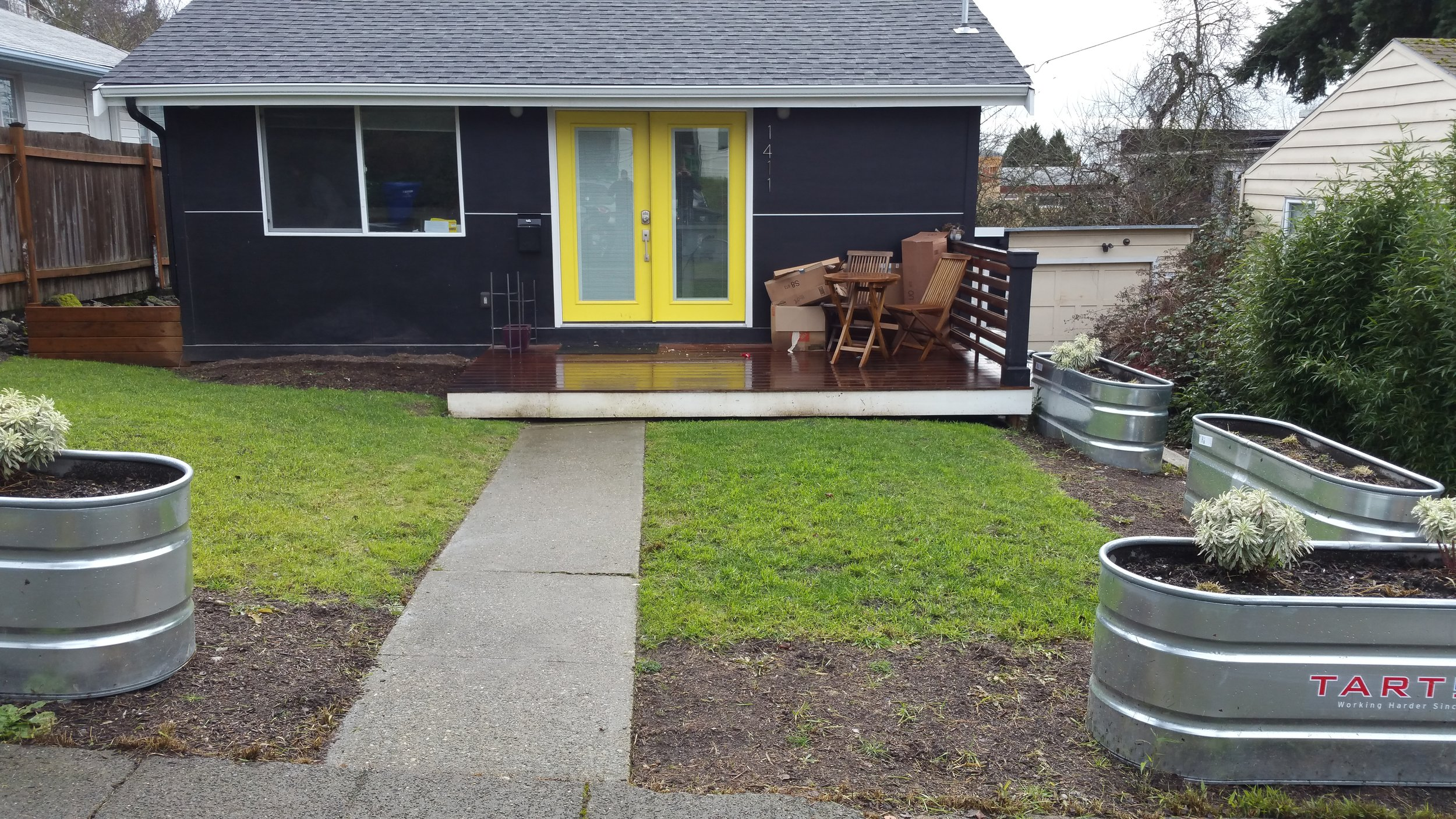 """A """"before"""" photo showing a lawn and horse trough garden beds."""