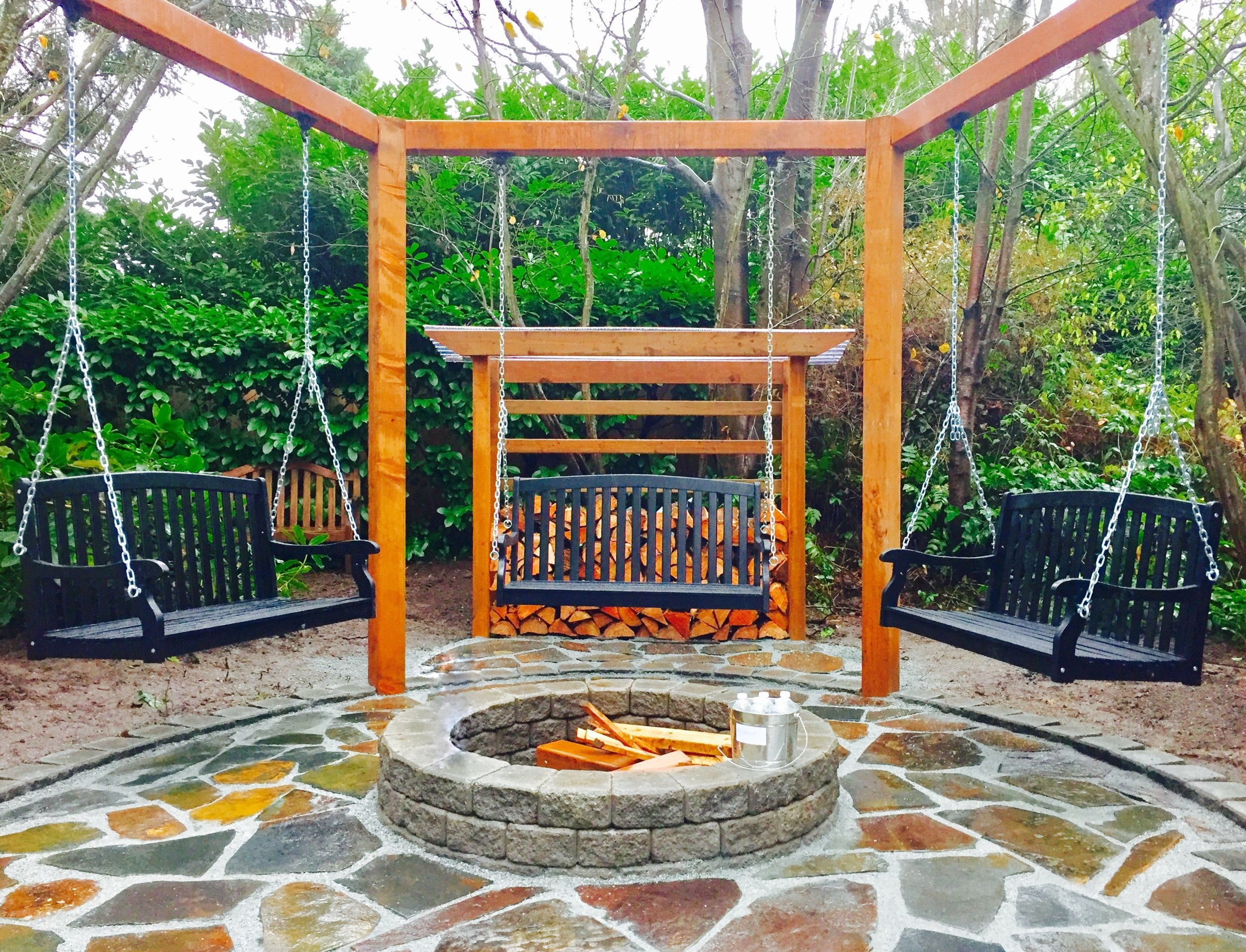 This   flagstone   patio features a three swing pergola and Roman stack stone fire pit.