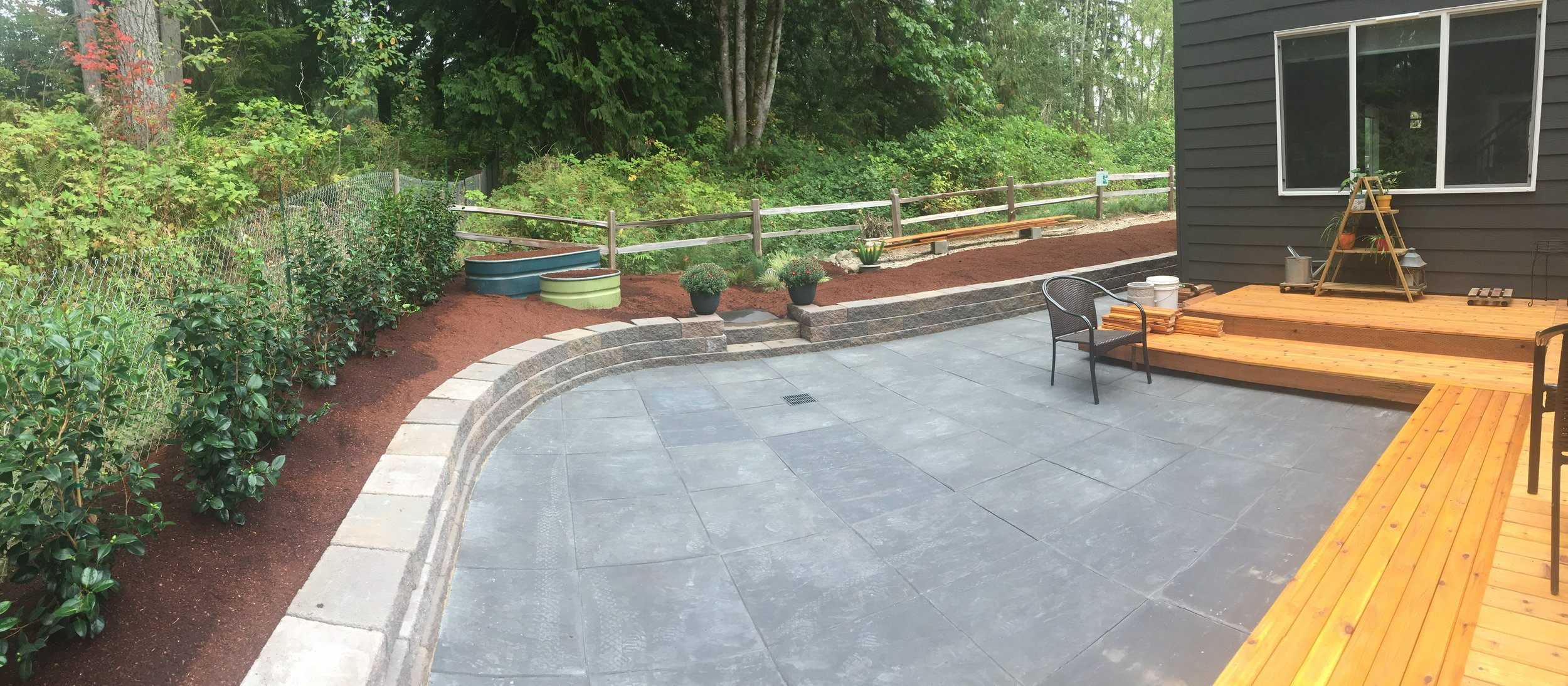 """This backyard patio, retaining wall and red bark garden beds is made with 24""""x24"""" charcoal glacier slate pavers, manor stone summit blend blocks, and drip irrigation along the garden beds and row of Camellia bushes."""
