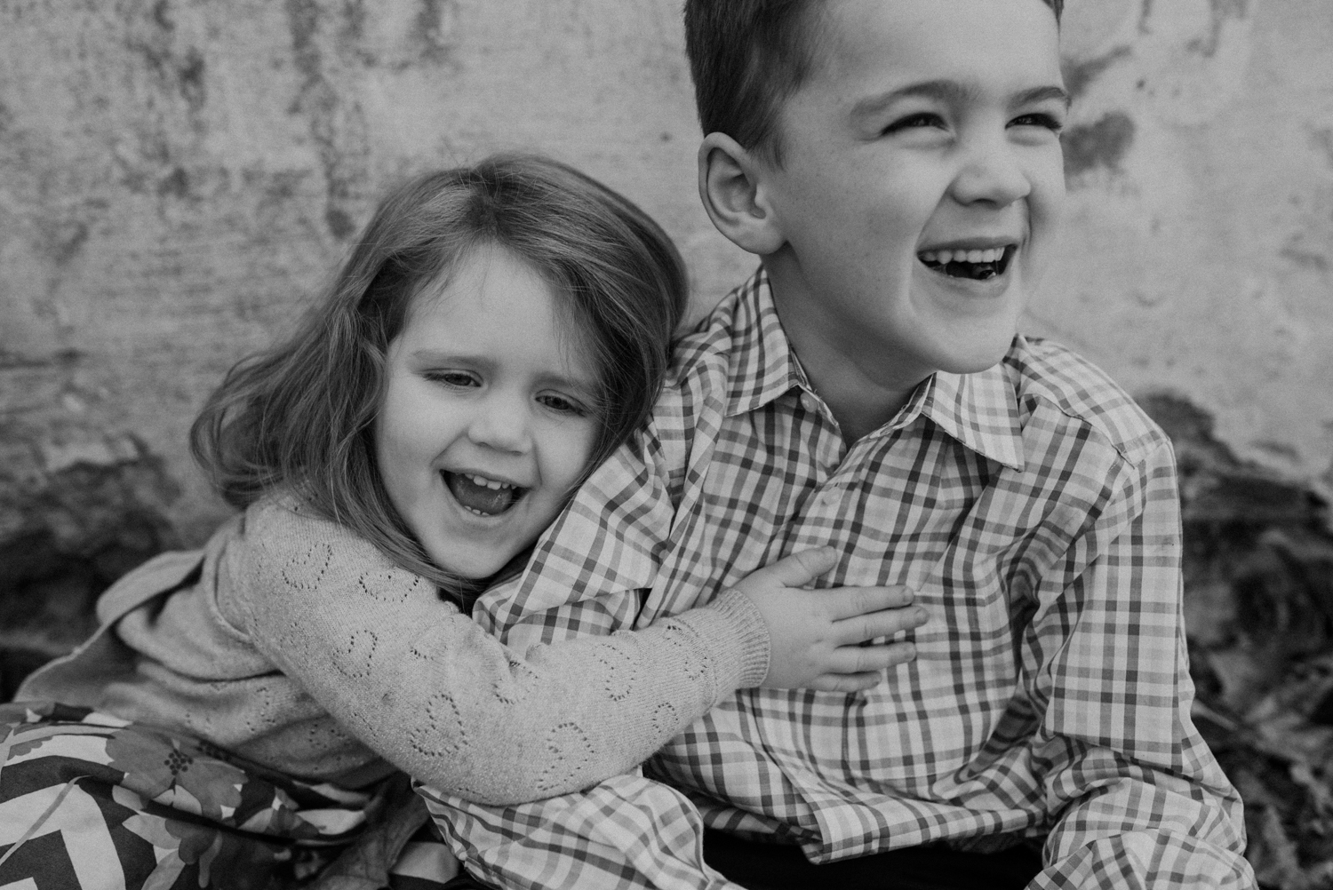black and white siblings laughing
