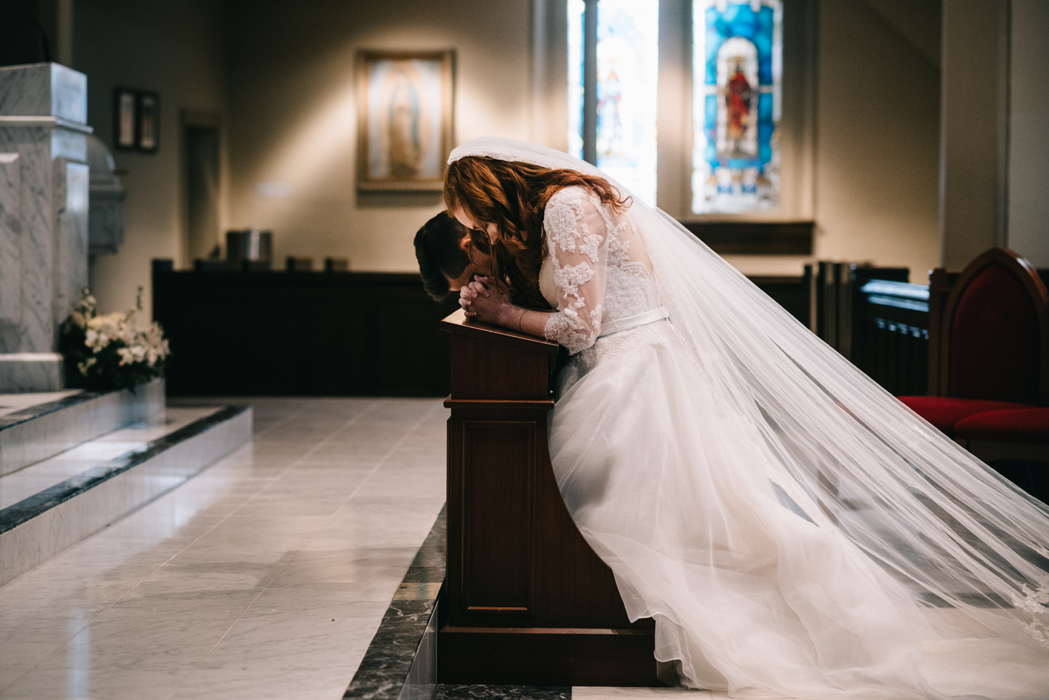 bride and groom pray during catholic wedding mass