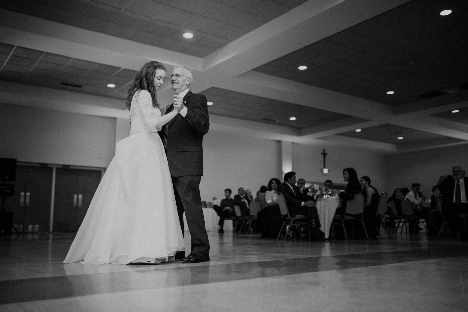 bride dances with father black and white