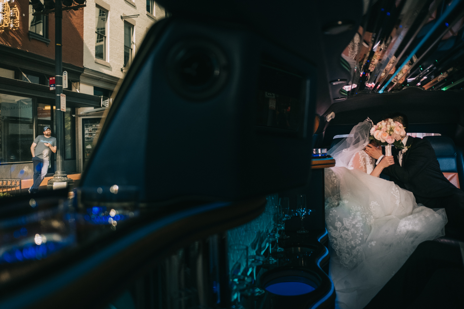 DC wedding couple in a Limo as street bystander looks on