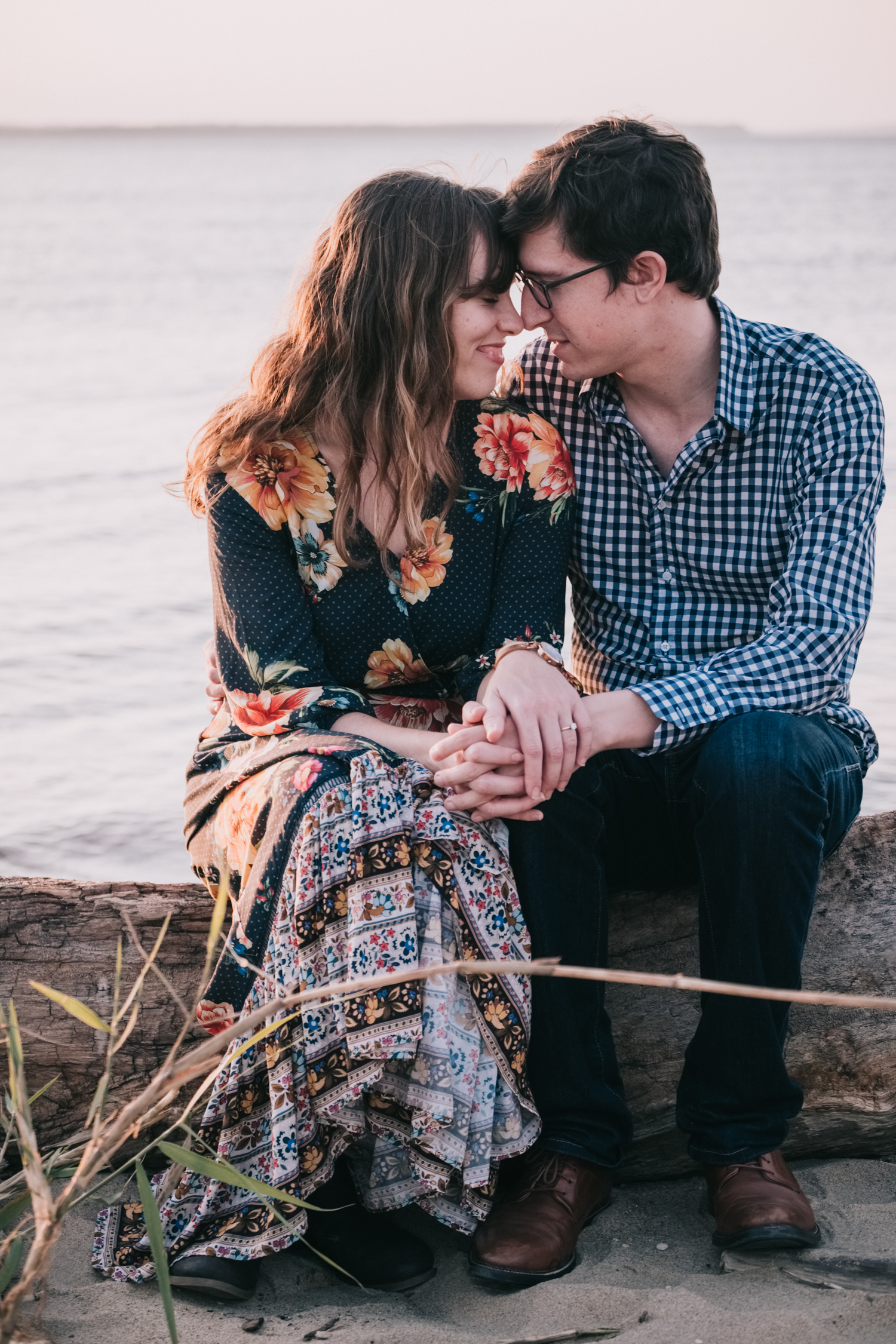 Engagement session sitting on the Chesapeake Bay at sunset