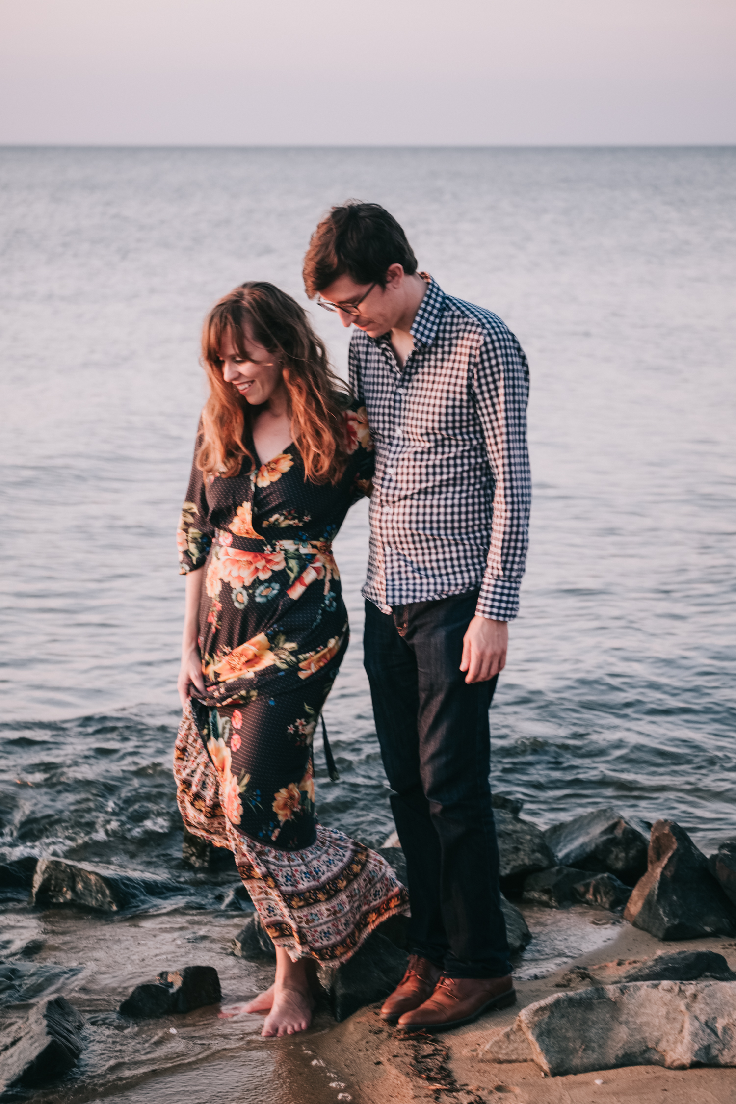 Maryland boho engagement couple walks in the water on the Chesapeake at sunset