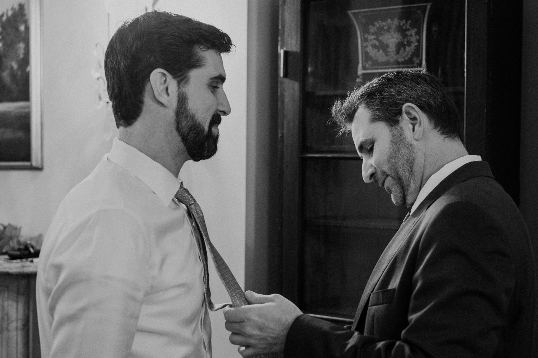 groom's brother helps tie his tie for wedding