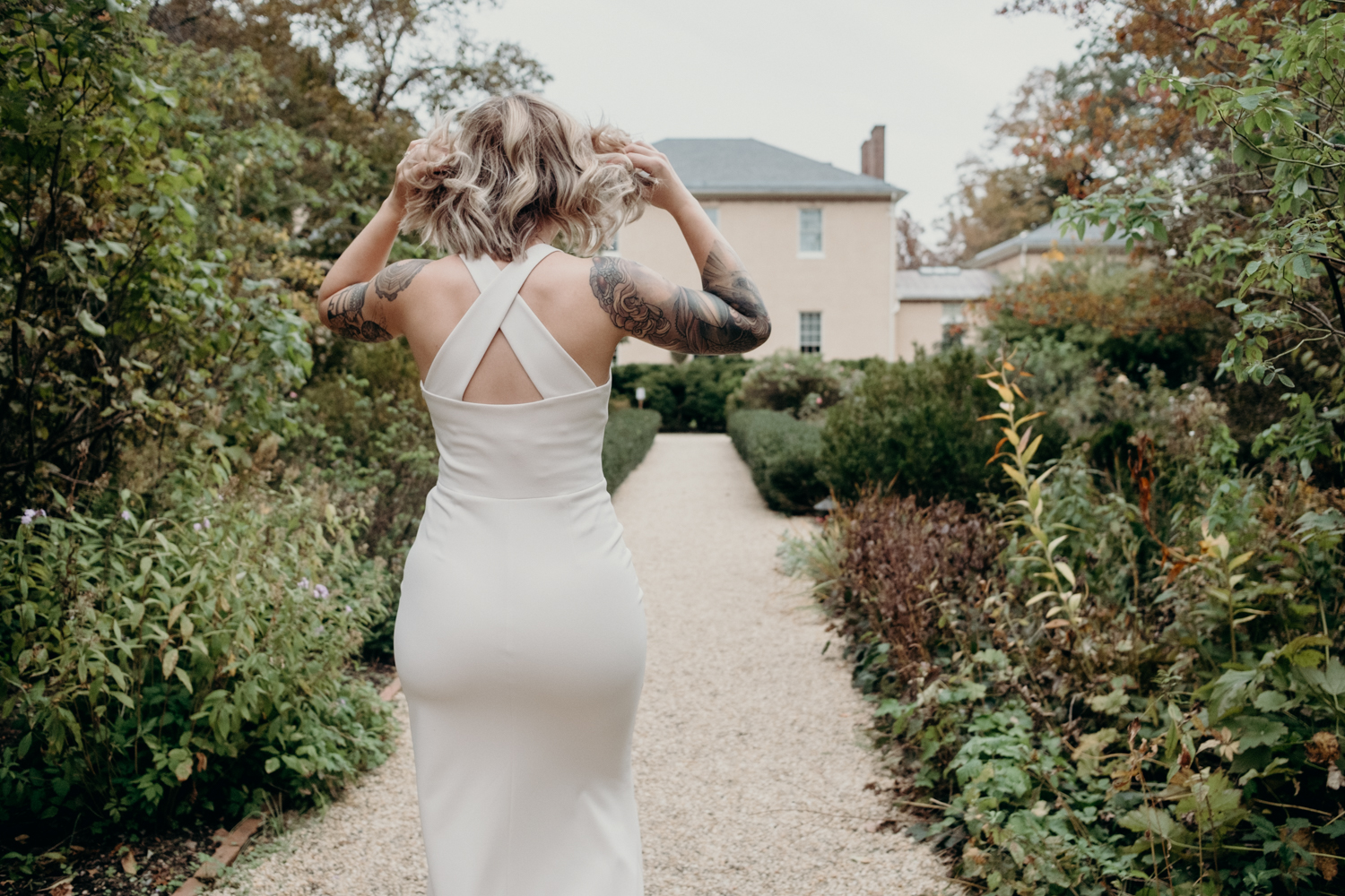 bride walks through gardens at tudor place for first look