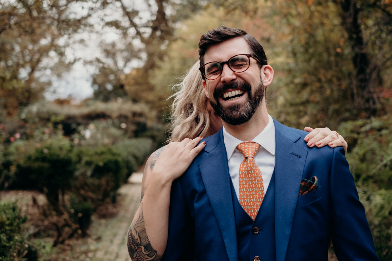 groom laughs with joy right before seeing his bride during their first look in dc intimate wedding