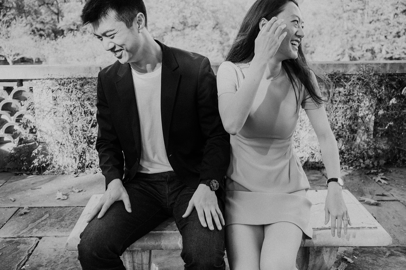 An engaged couple laughs while seated on a park bench in the gardens at Dumbarton Oaks.