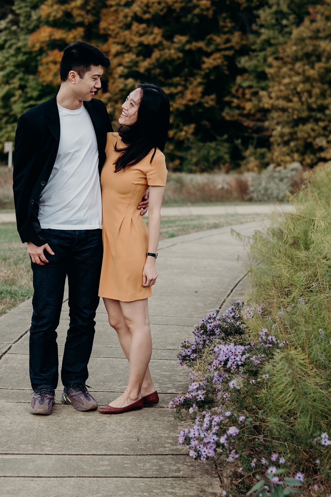 An engaged couple walks along a garden path at the National Arboretum.