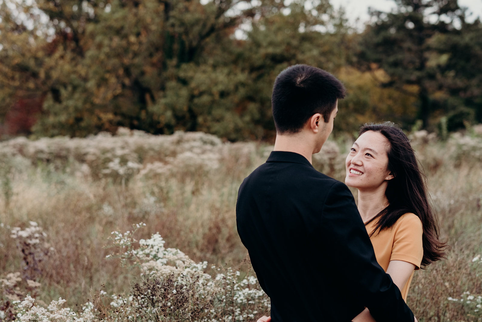 An engaged couple embraces in a field of wildflowers at the National Arboretum.