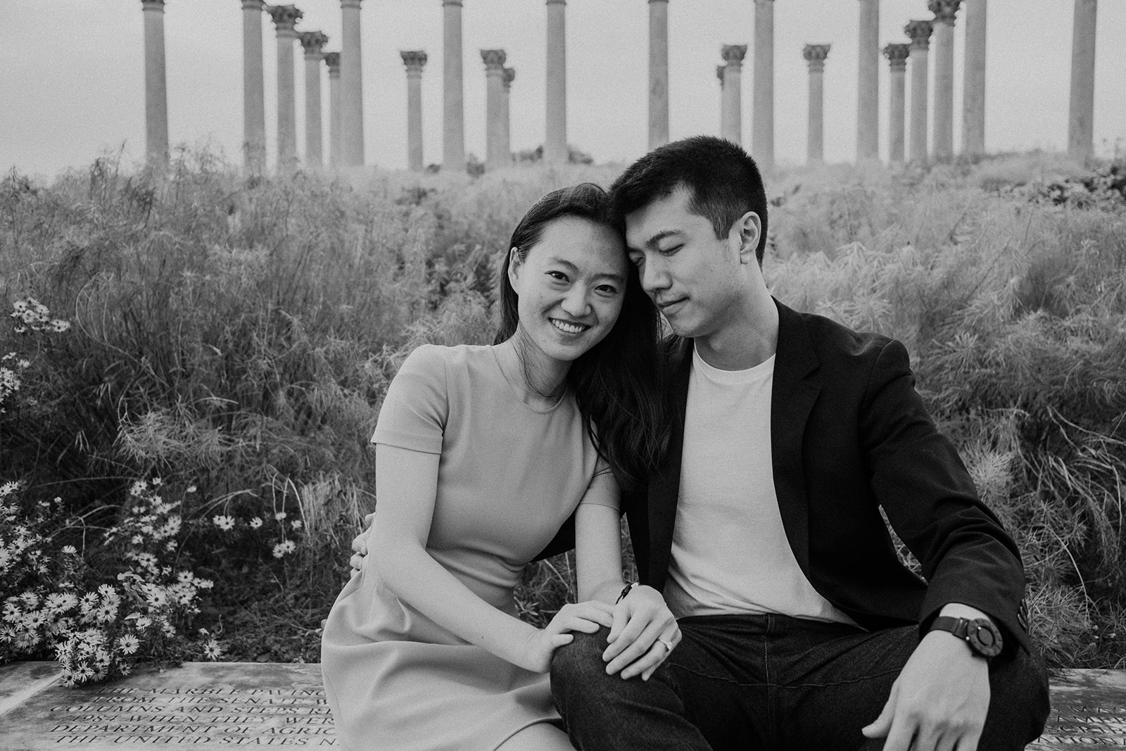 A woman rests her head on her fiancé's shoulder near the pillars at the National Arboretum.