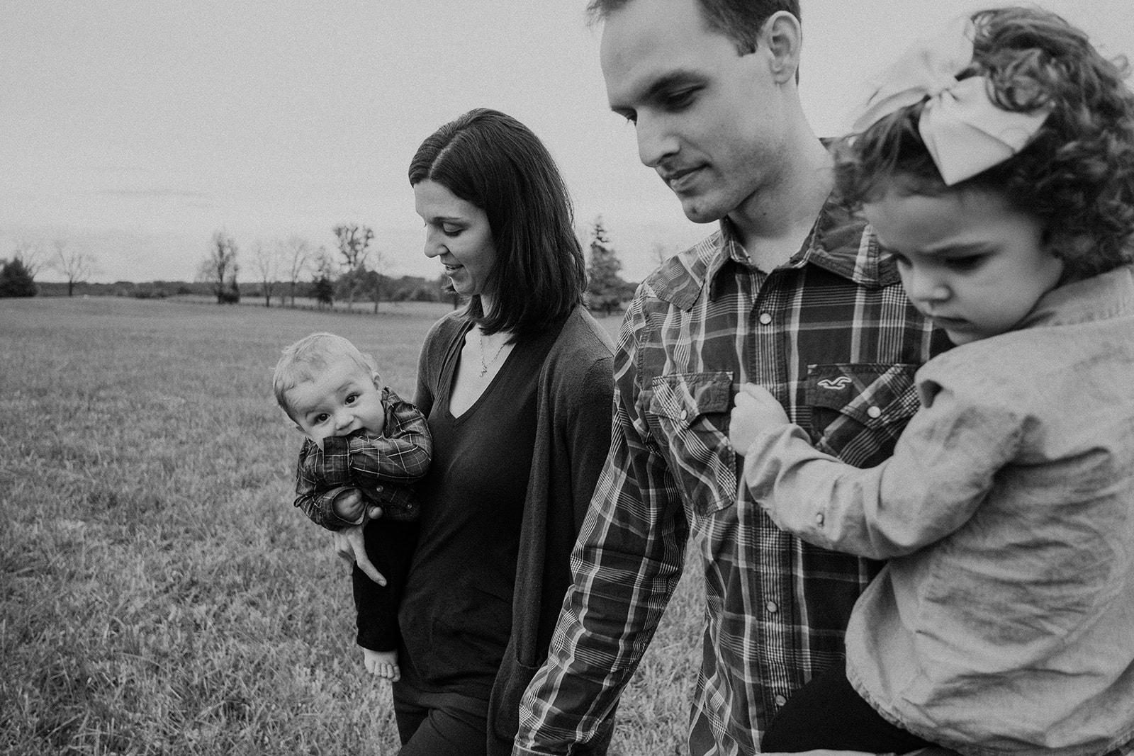 A family walks through a field at Morven Park.