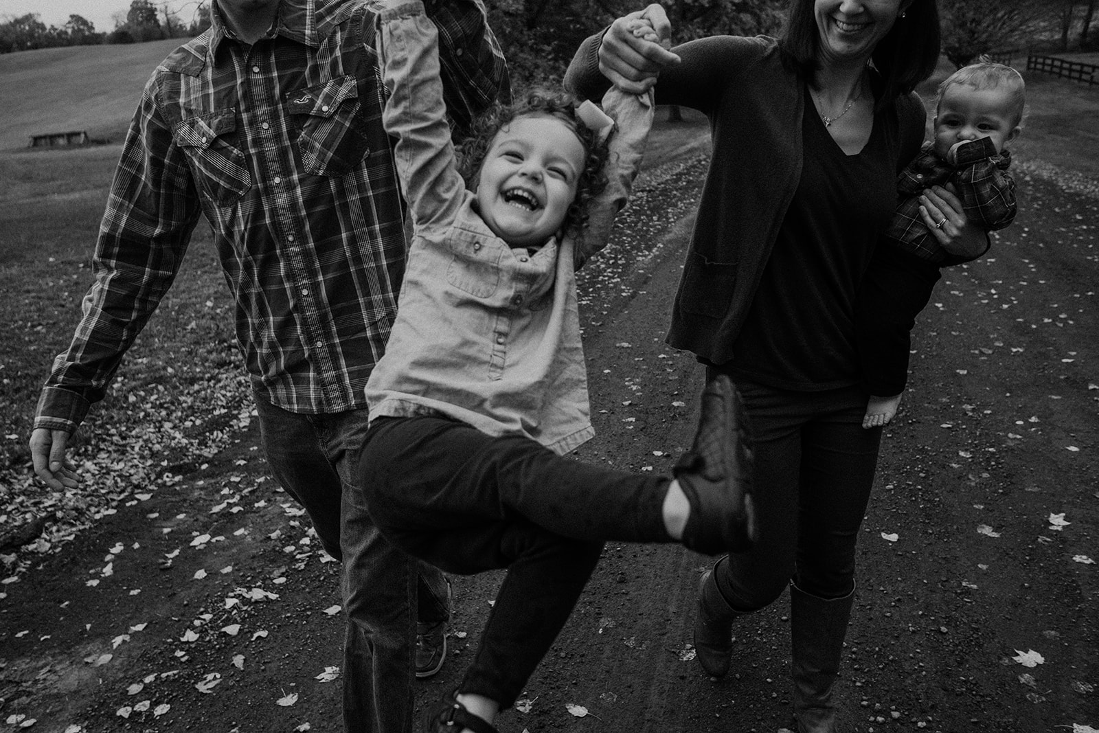 A little girl giggle joyfully as she is swung by her parents walking through Morven Park.