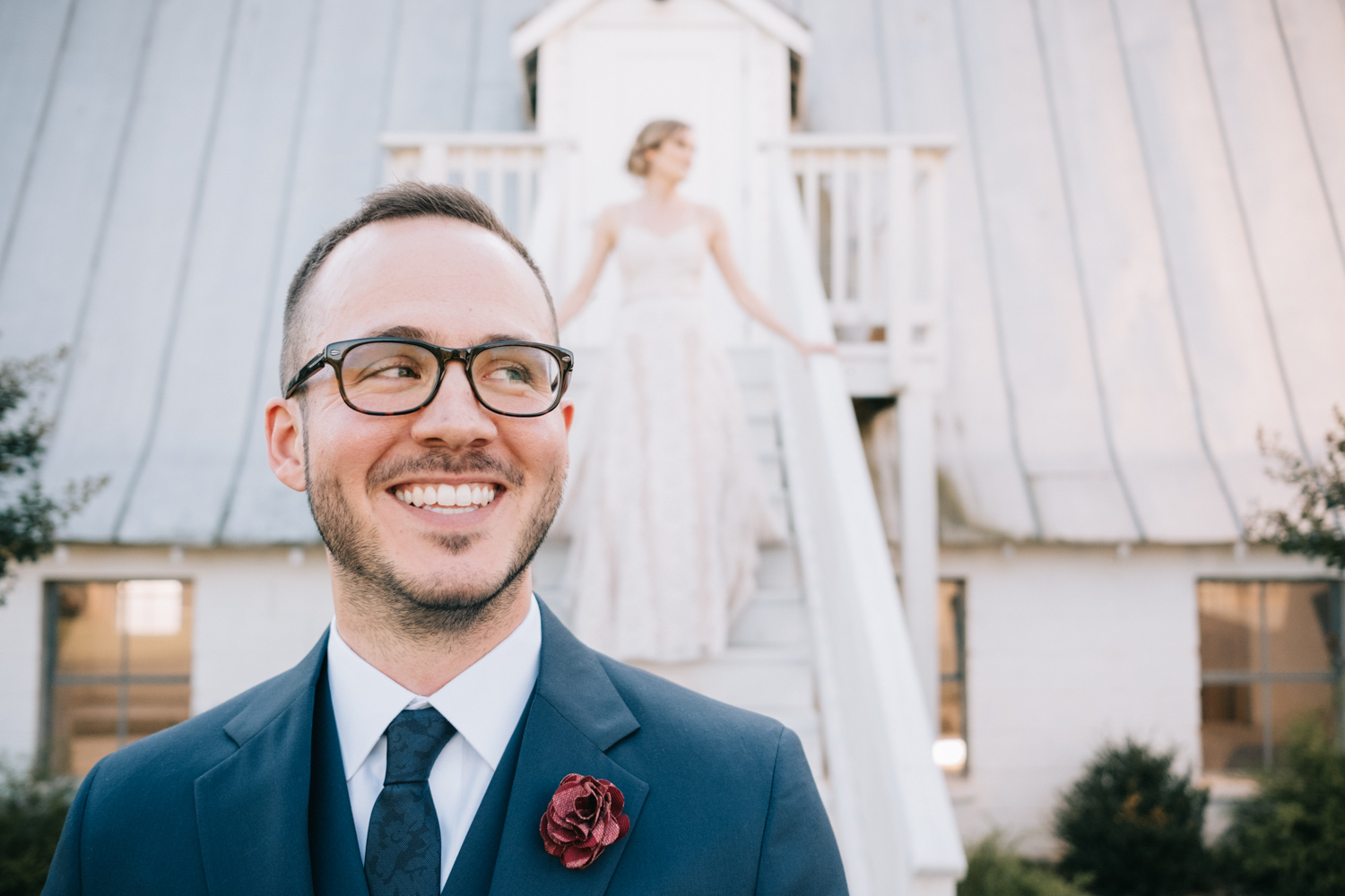 Groom smiles as he hears his bride walk down the stairs for First Look