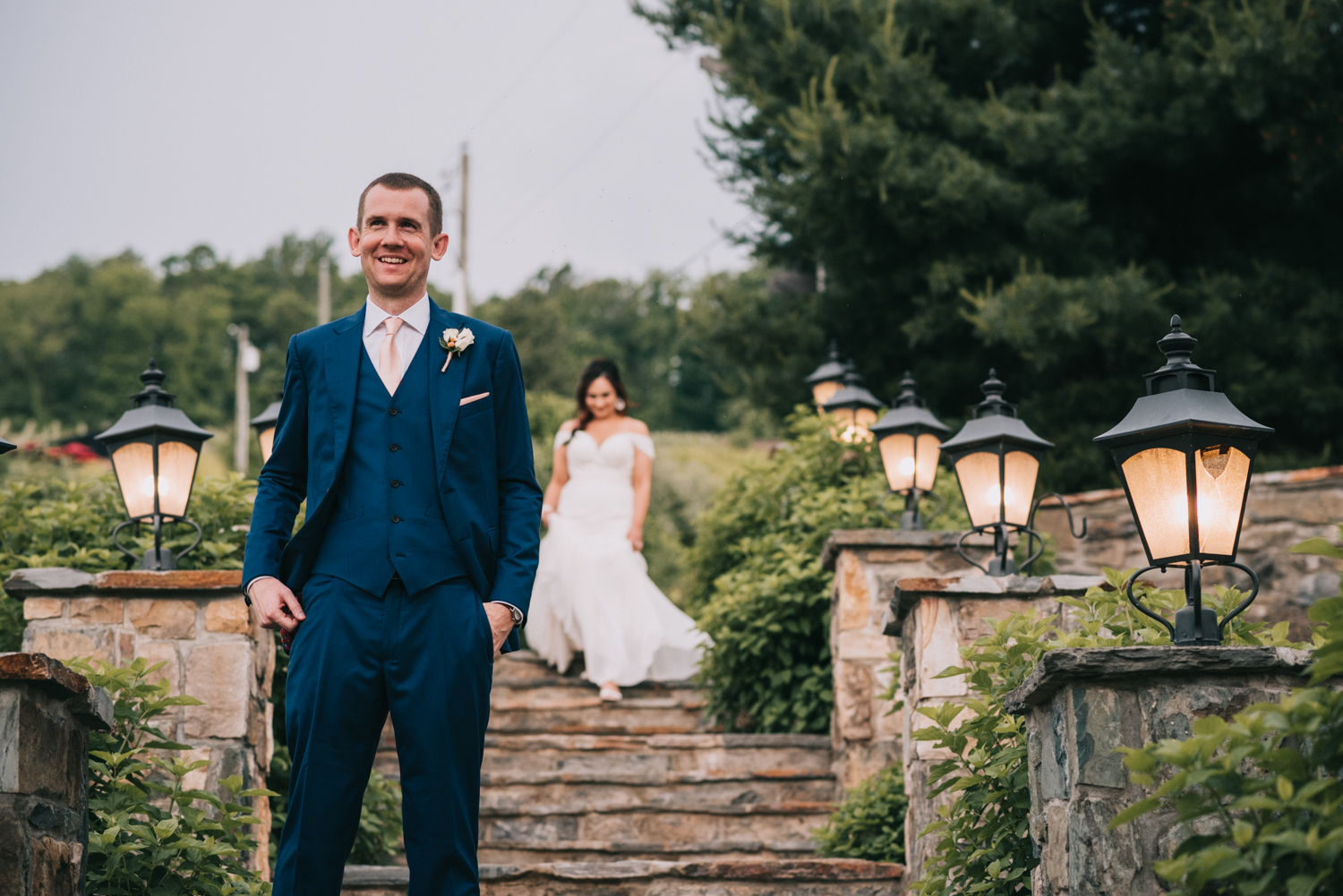 groom waits as bride walks down steps to meet him during first look at Bluemont Vineyard