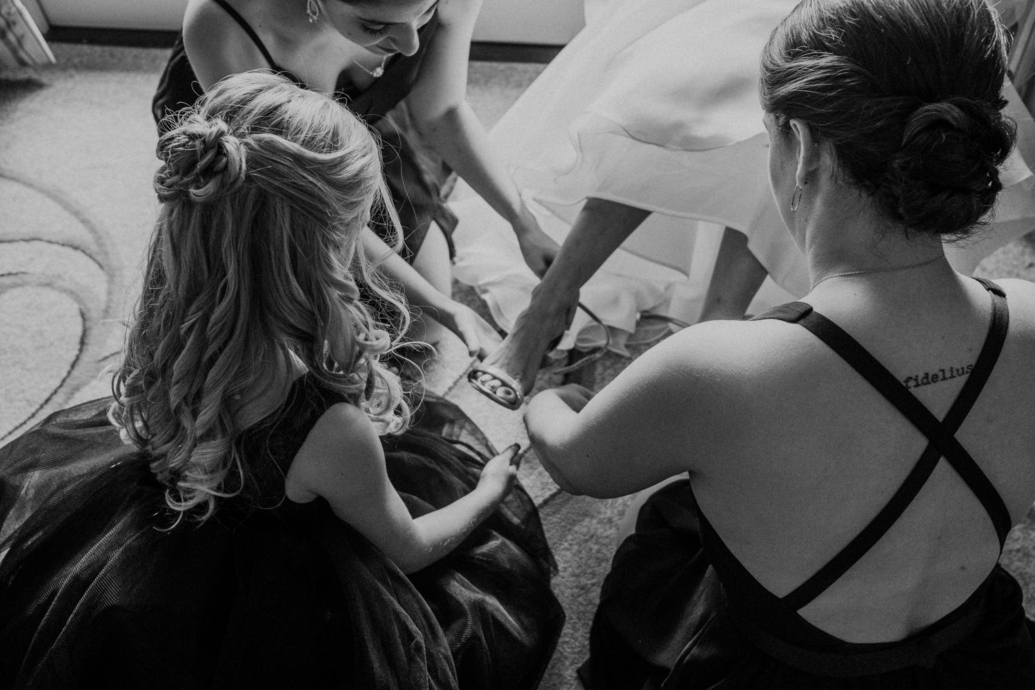 bridesmaids help put the bride's shoes on before virginia wedding