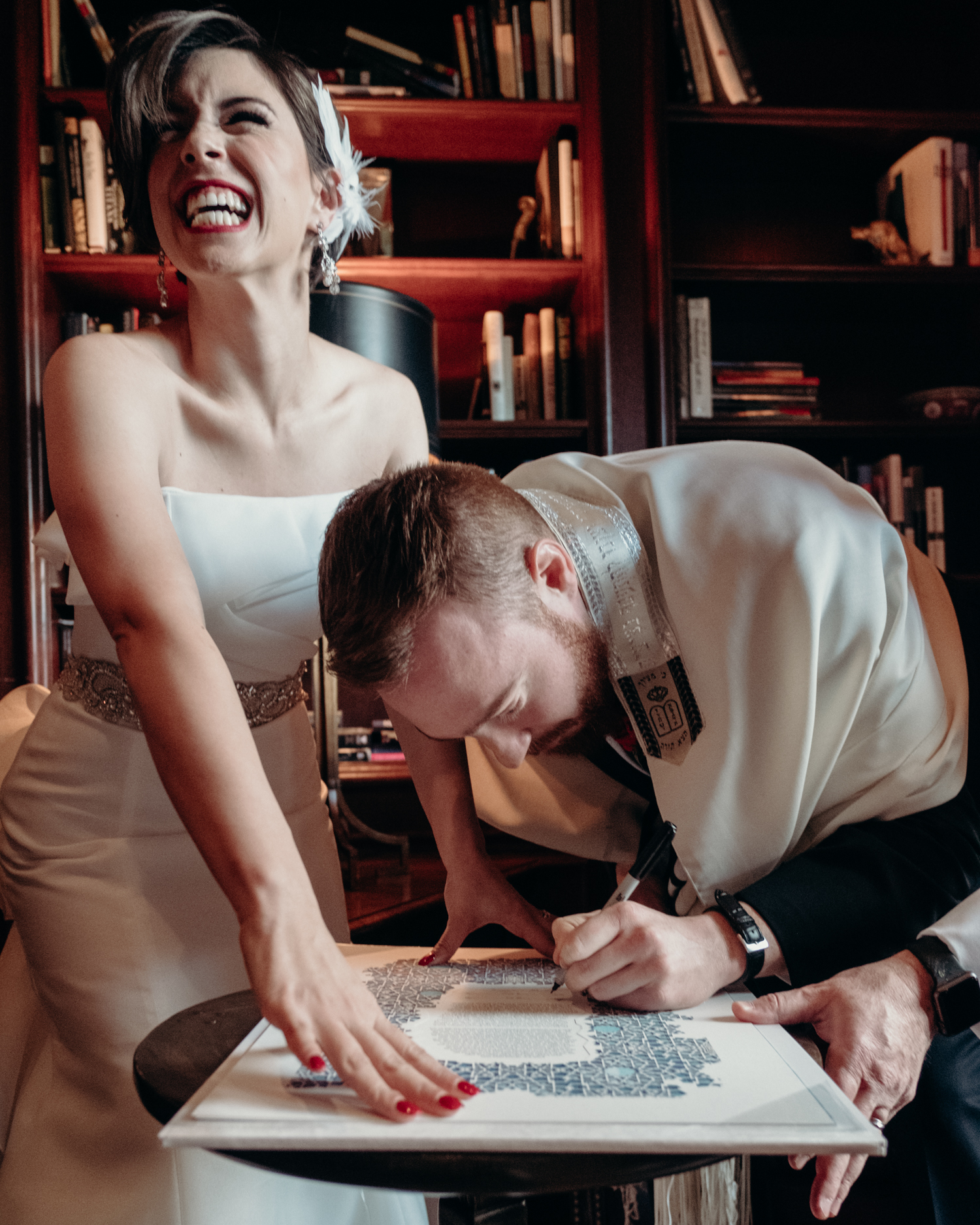 Bride smiles big as groom signs the ketubah at Virginia jewish wedding