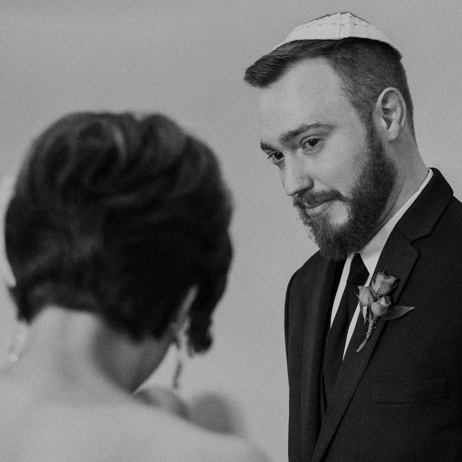 groom watches bride as tears roll down his face during vows