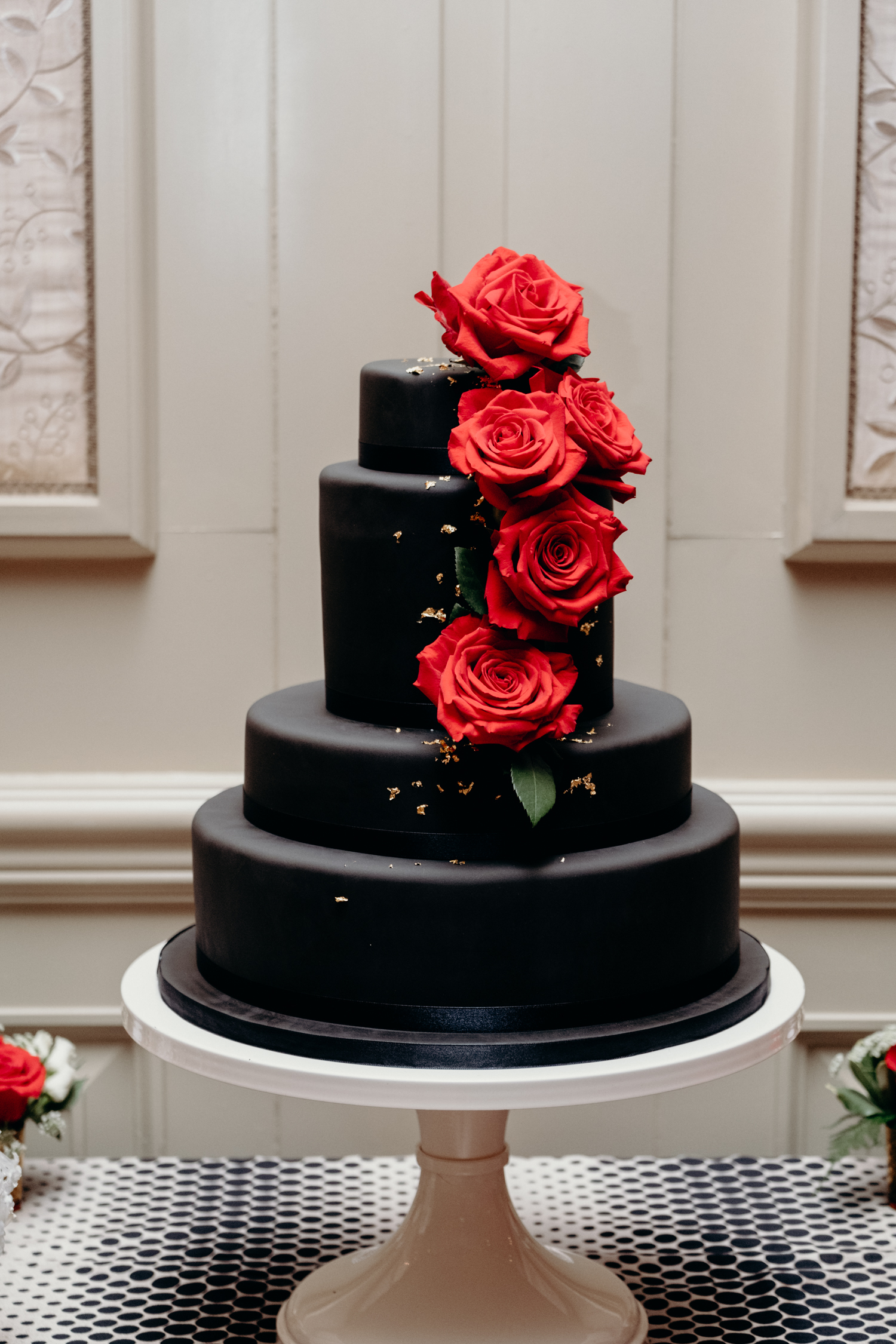black and gold cake with red roses at virginia wedding