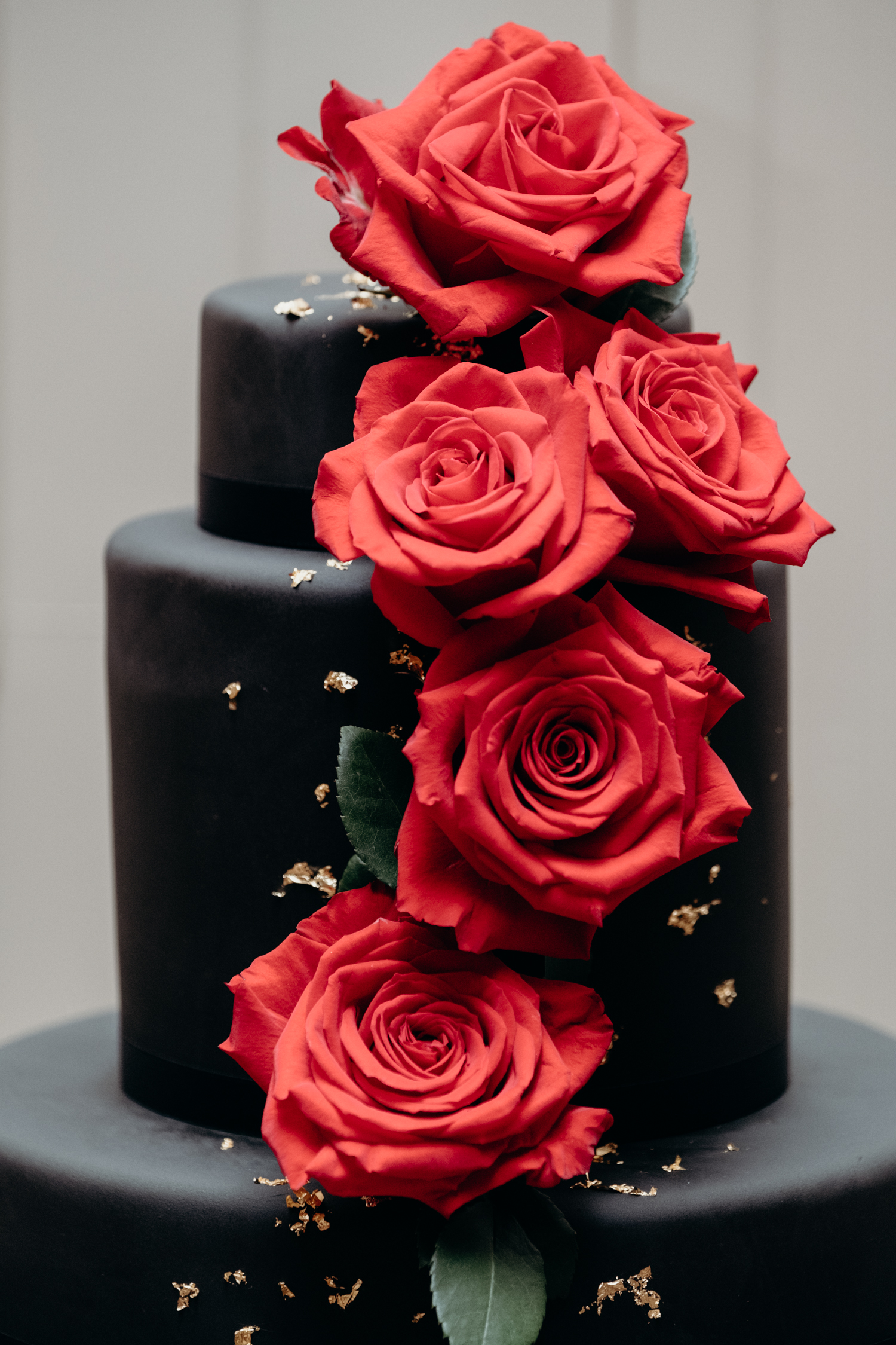black and gold cake with red roses up close at middleburg wedding