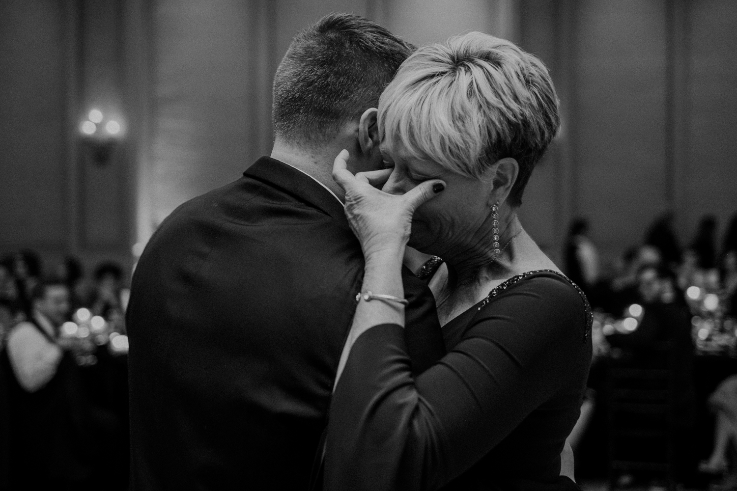 mother of groom wipes tears from her eyes during mother son dance at virginia wedding