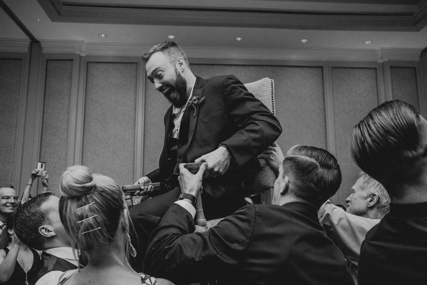 groom is lifted in his chair during the hora at Salamander Resort wedding