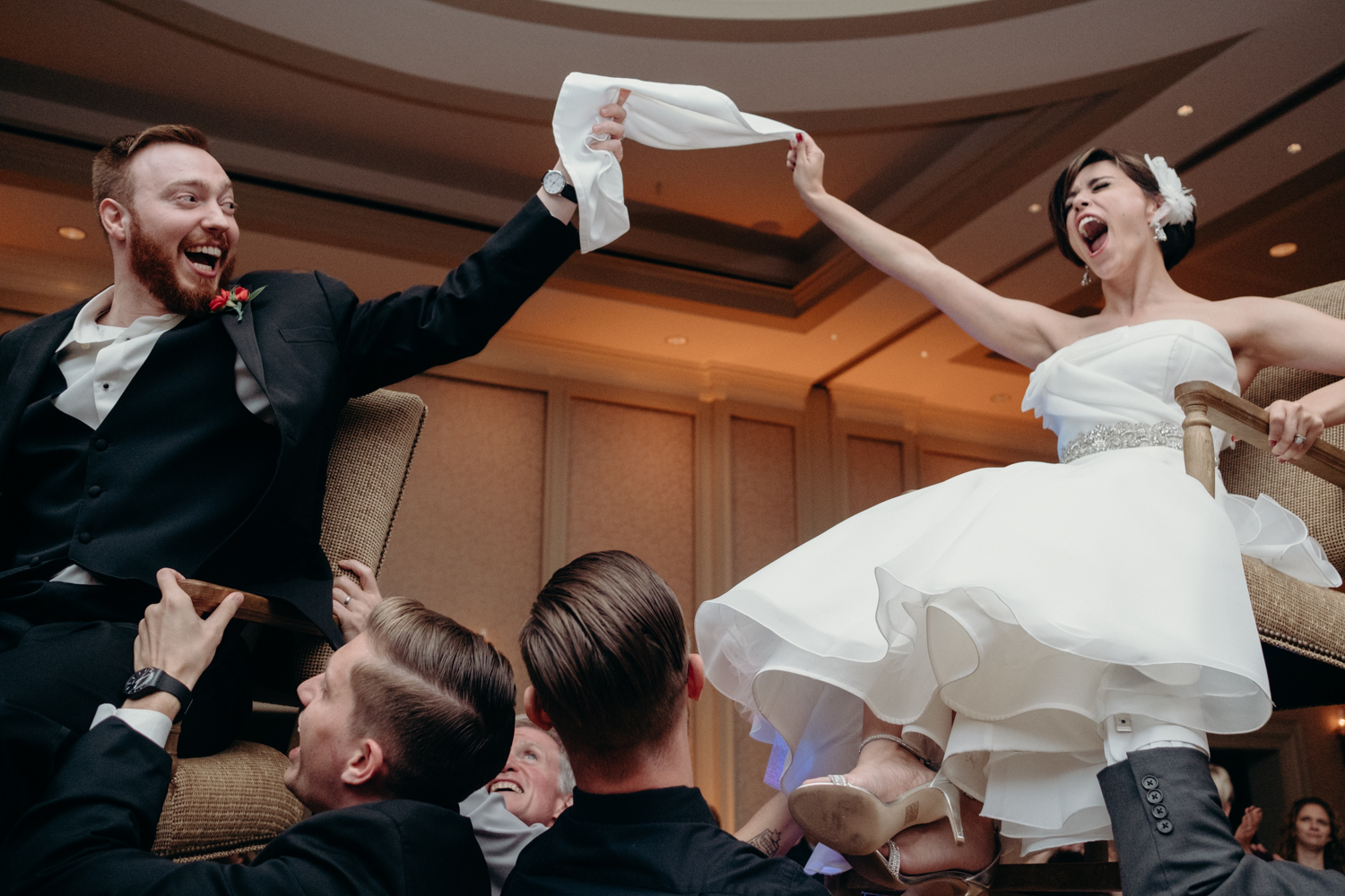 bride and groom in the air during fun hora dance at Virginia Jewish wedding