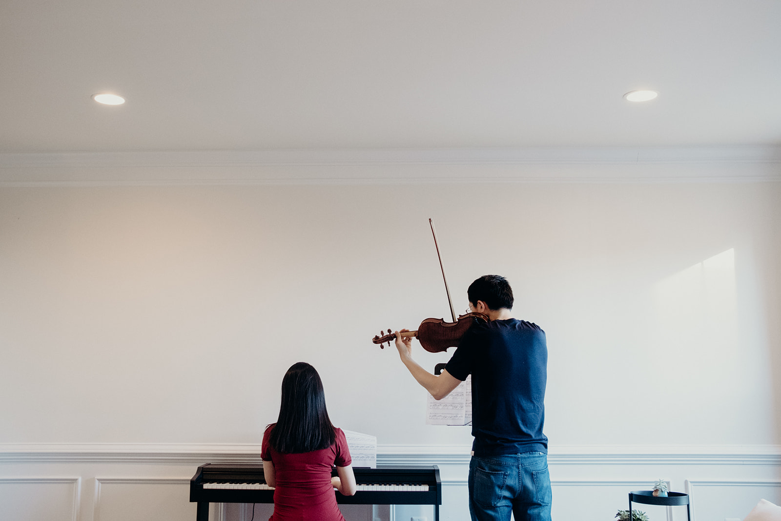A couple plays music together. The wife plays the piano and the husband plays the violin in their first home together.