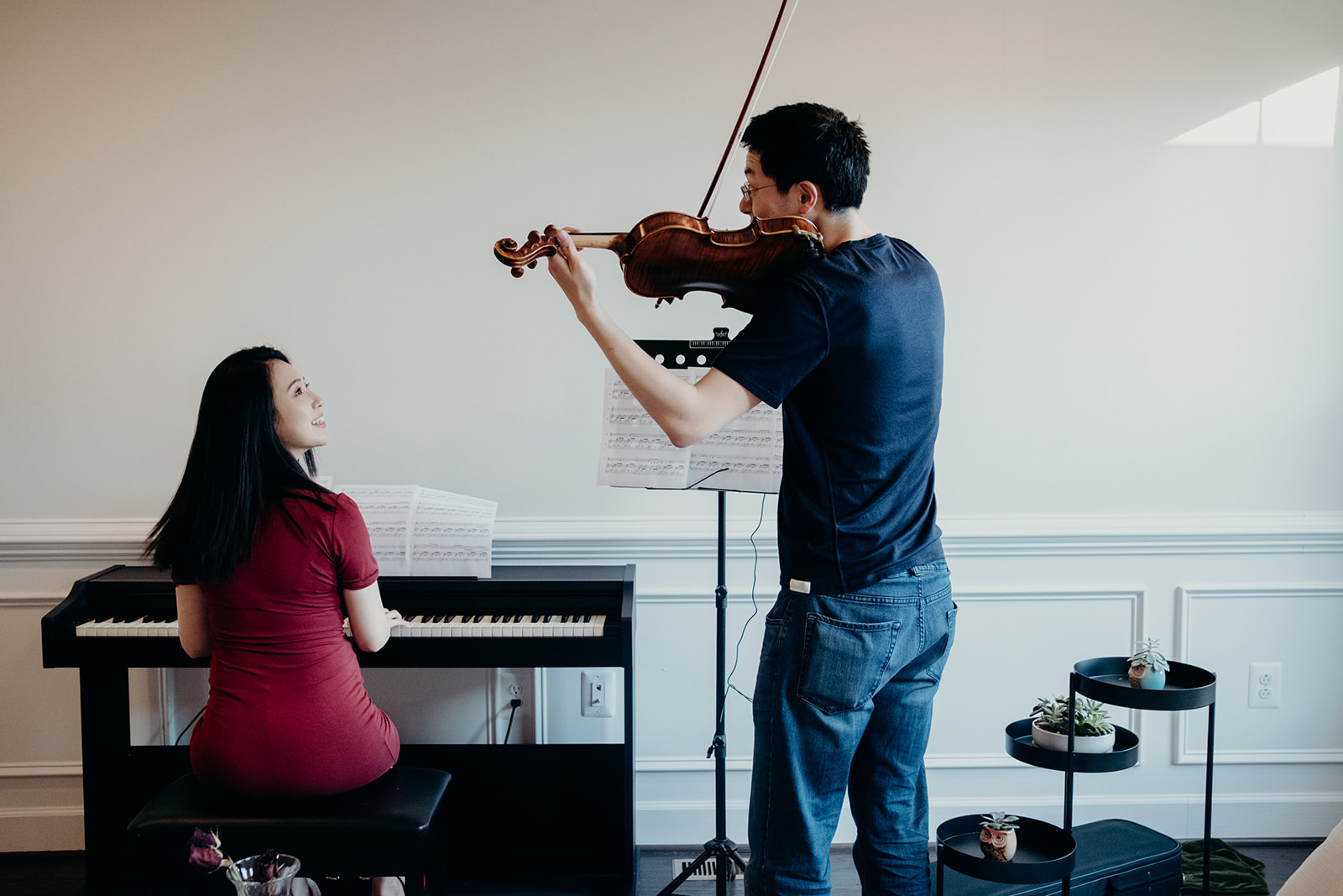 An couple expecting their first child play music together. The pregnant mother plays the piano while her husband plays the violin.