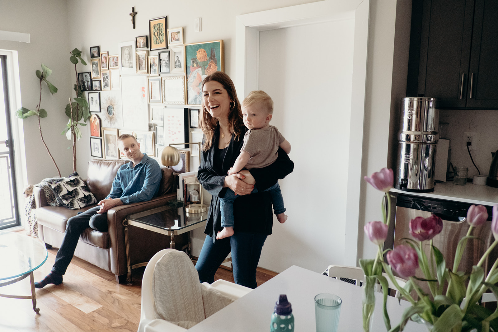 A woman holds her infant son and laughs while her husband looks on in their apartment.