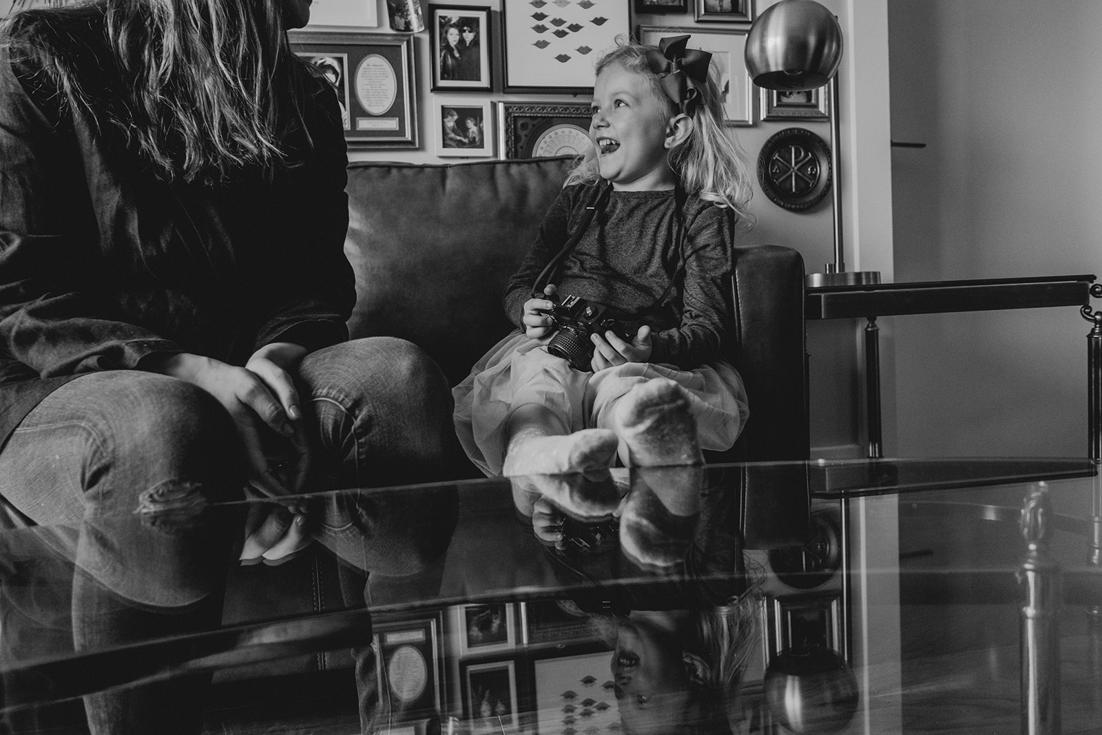 A little girl laughs while seated on a couch next to her mother in their apartment in Washington, DC.