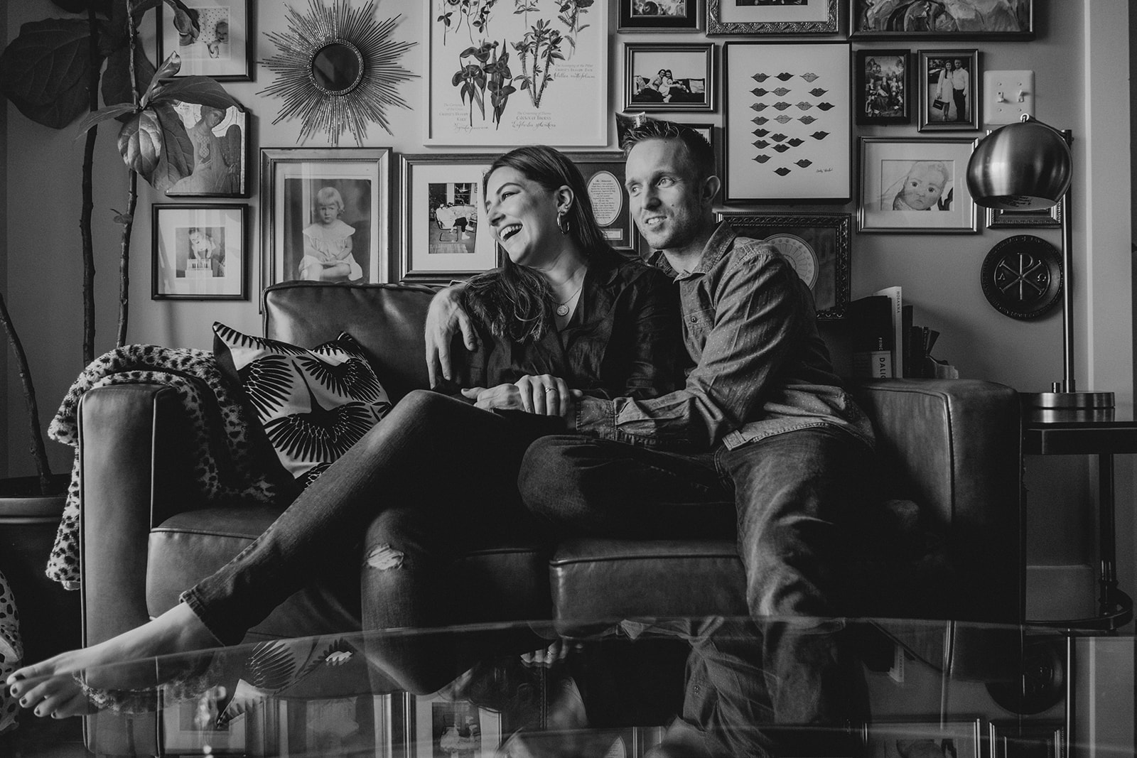 A husband and wife laugh together while sitting on a couch in their apartment in Washington, DC.