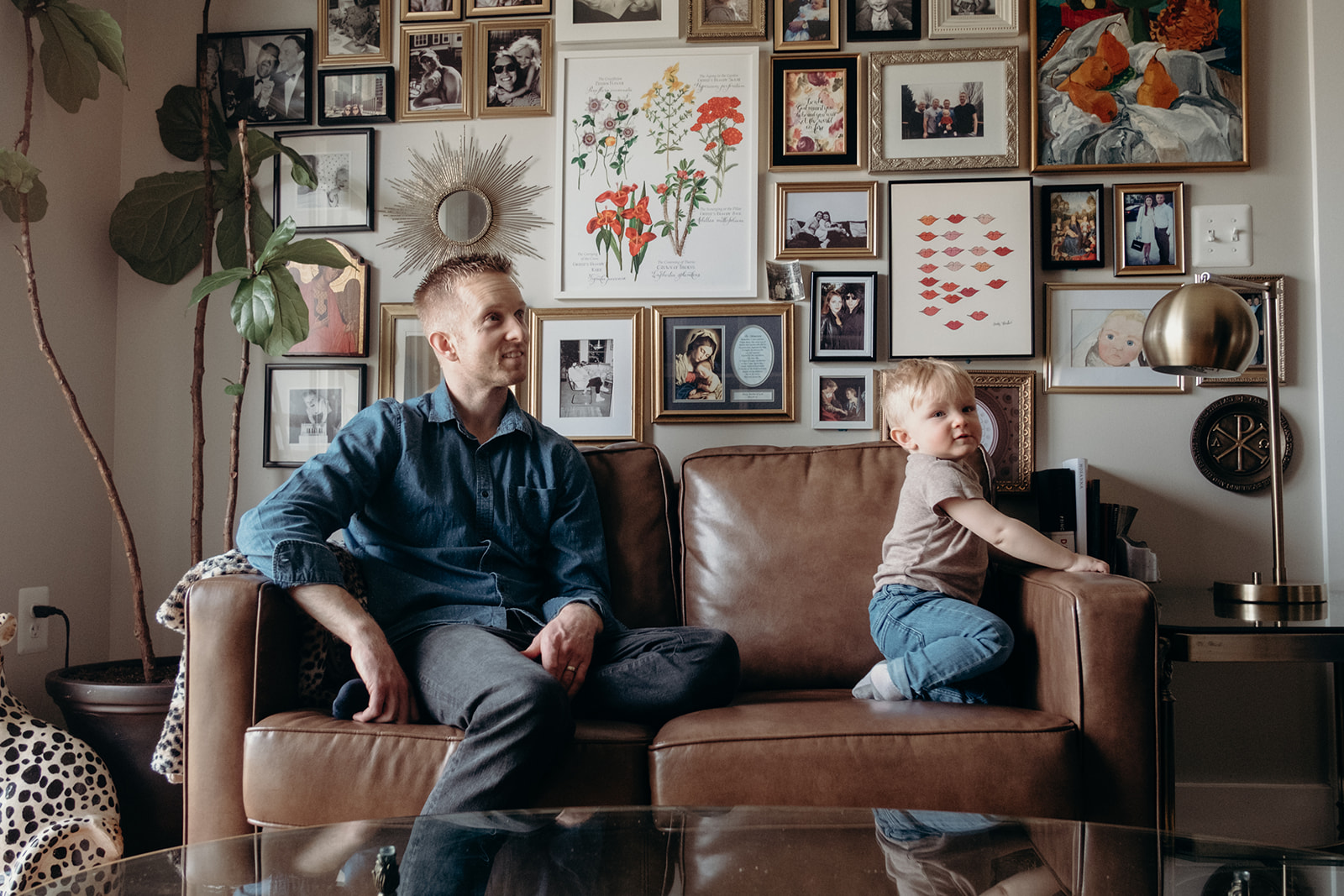 A father and son sit on a couch in their apartment in Washington, DC.
