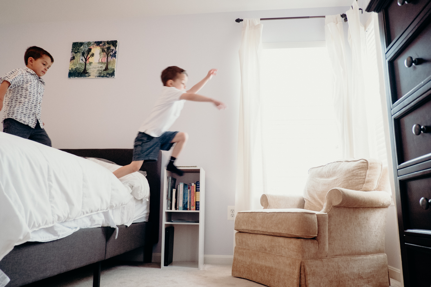 A little boy jumps off his parents bed onto a chair while his little brother watches.