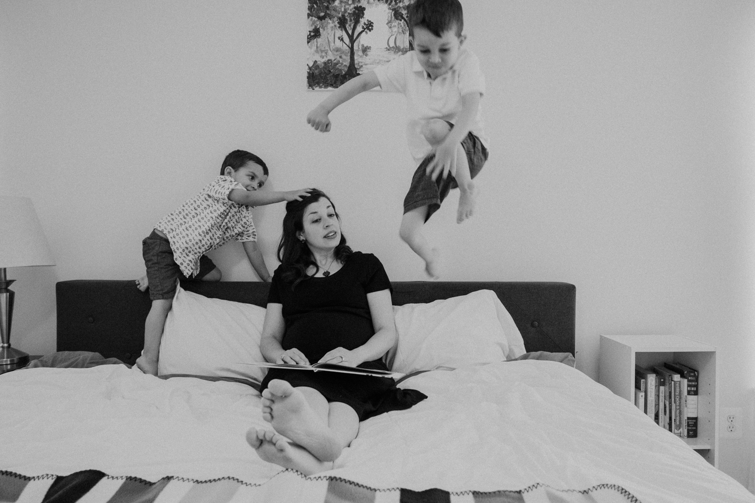 A boy jumps over his mother onto her bed while she looks on.