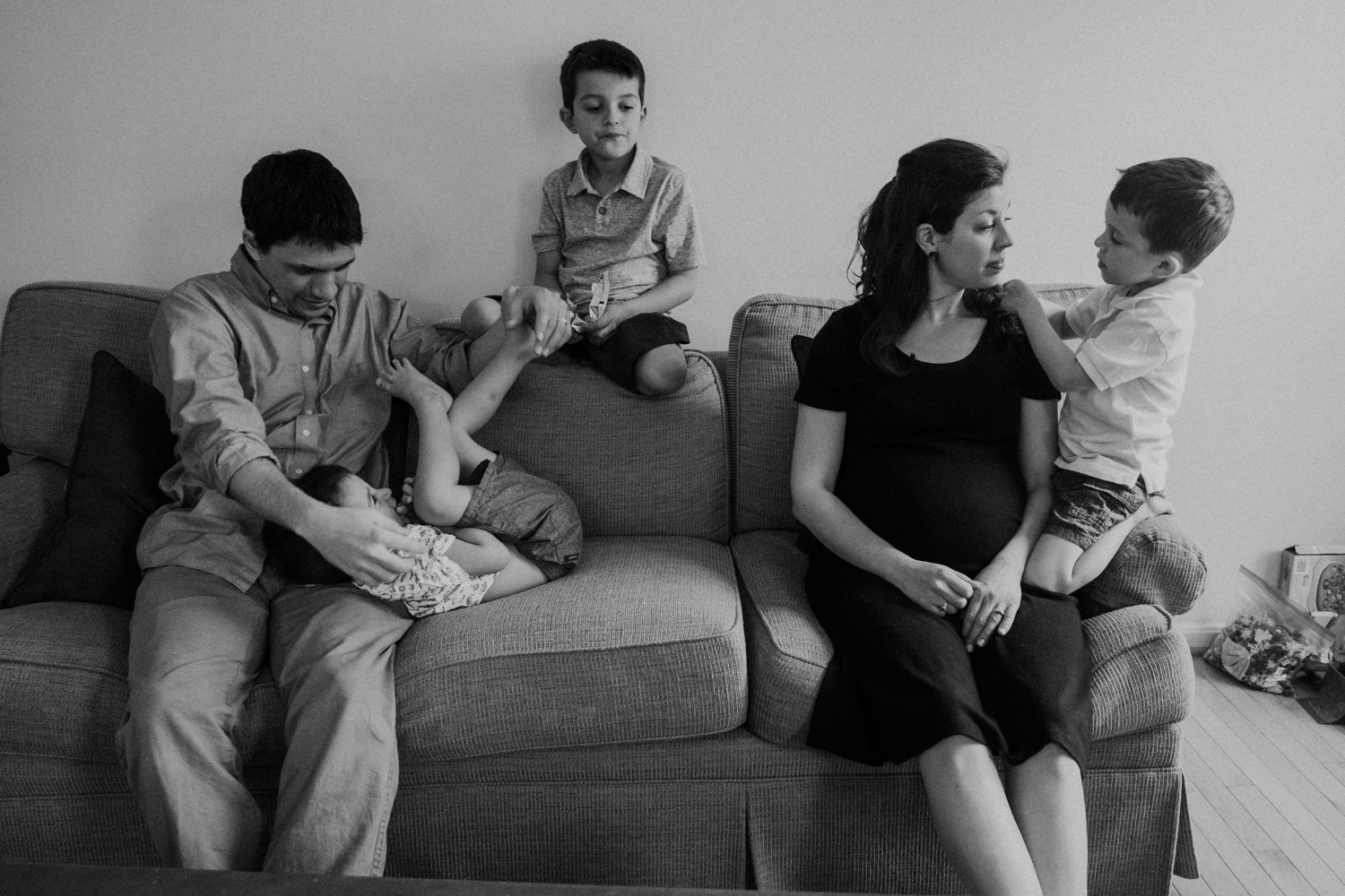 A mother and father are surrounded by their 3 boys while expecting their fourth child.