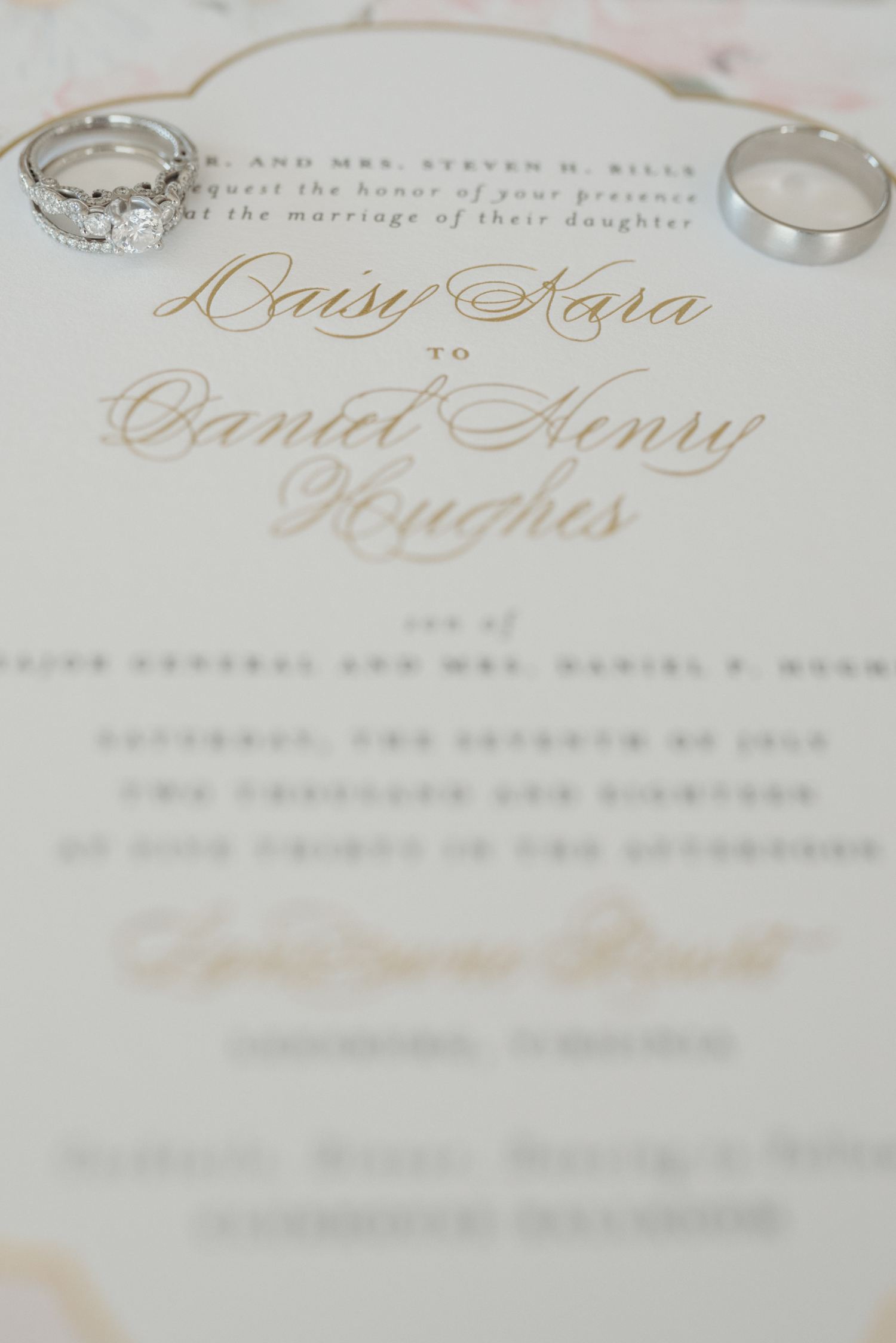 A couple's wedding rings sit on their wedding invitation.