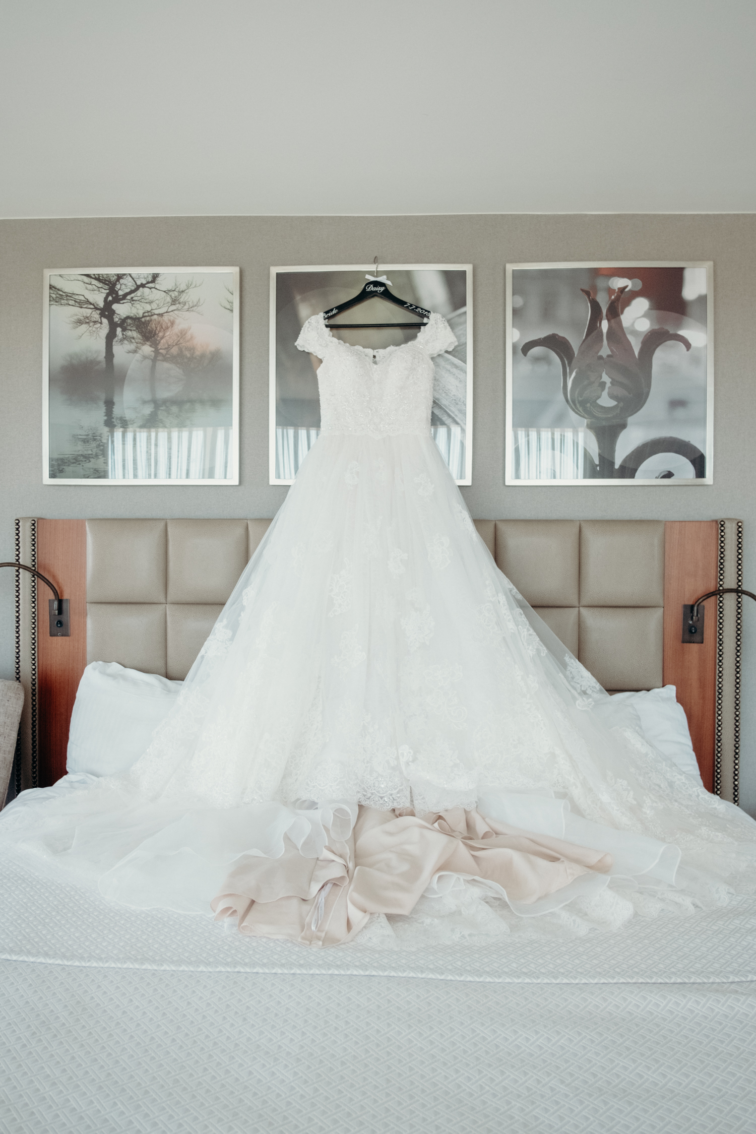 A bride's a-line wedding dress hangs above a bed at Lansdowne Resort.