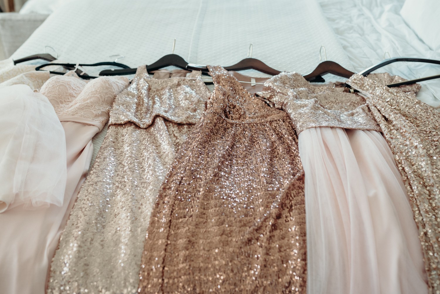 A slew of sparkly bridesmaids dresses wait on the bed before a wedding at Lansdowne Resort.