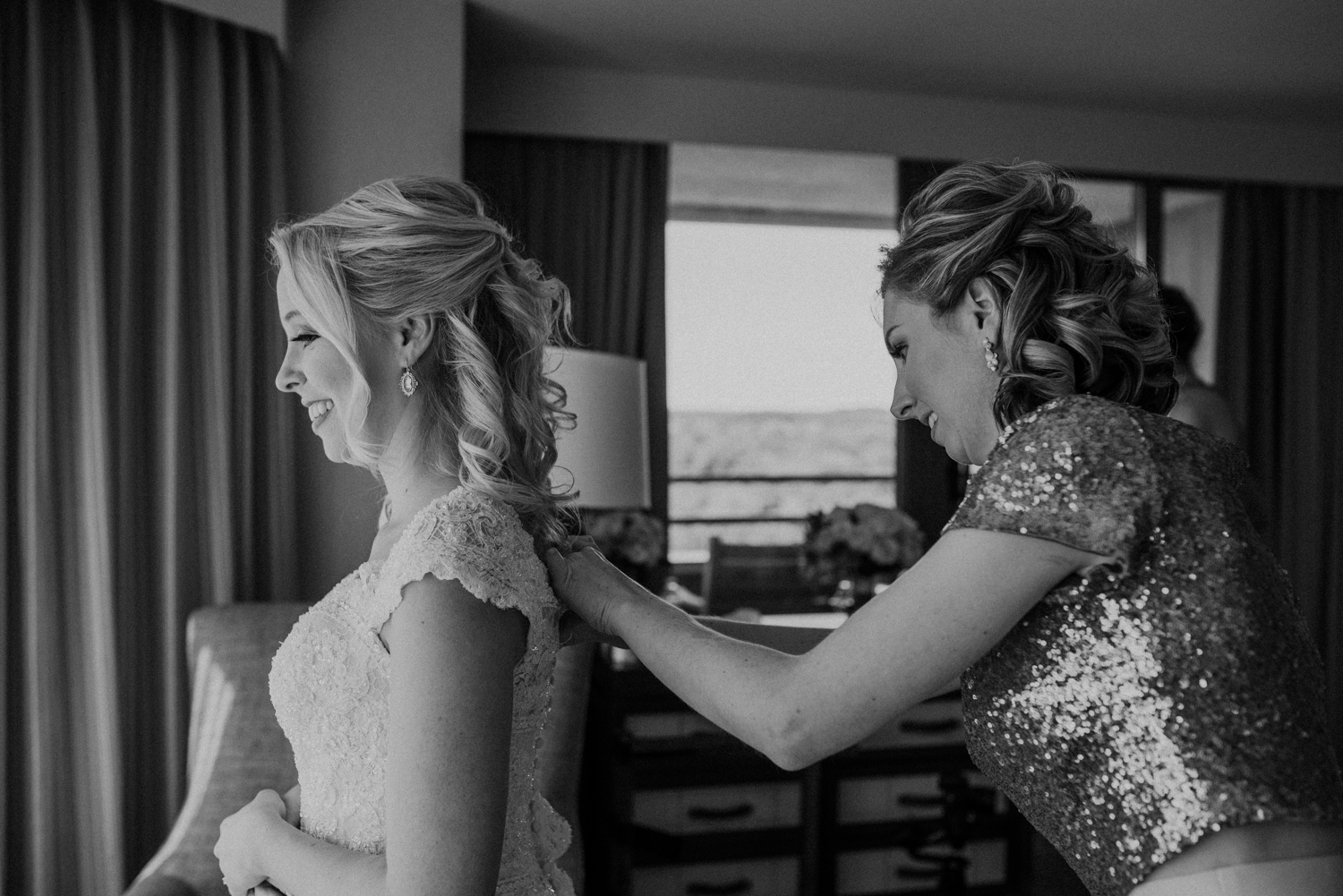 A maid of honor helps the bride get her dress on for her wedding day at Lansdowne Resort.