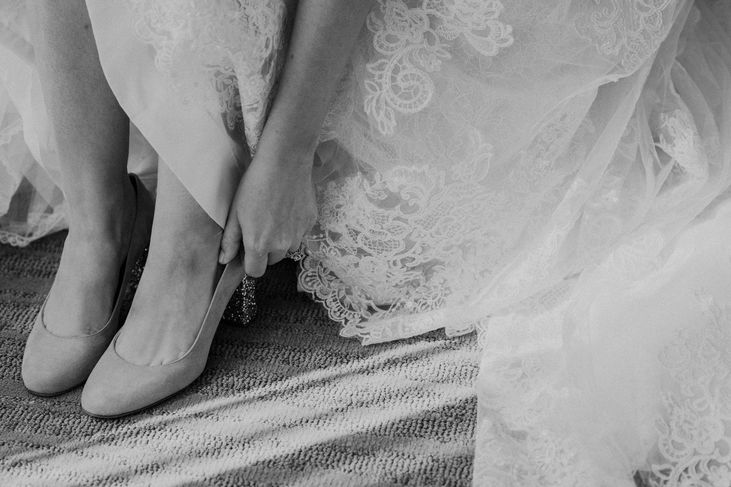 A bride puts on her shoes before her wedding at Lansdowne Resort.