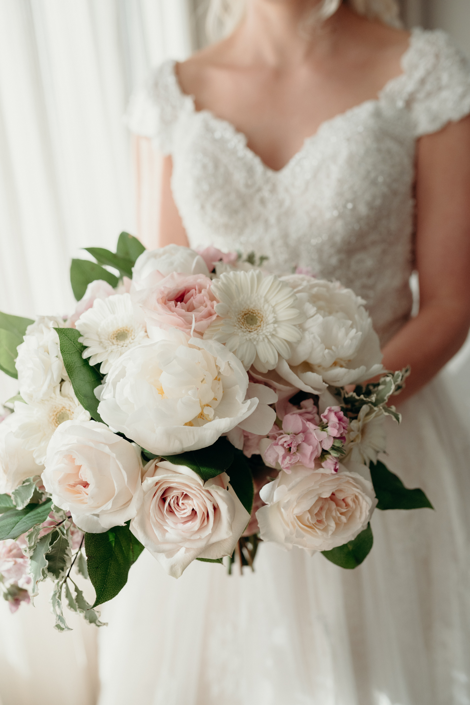 A bride holds a bouquet of of pink and white flowers on her wedding day at Lansdowne Resort.