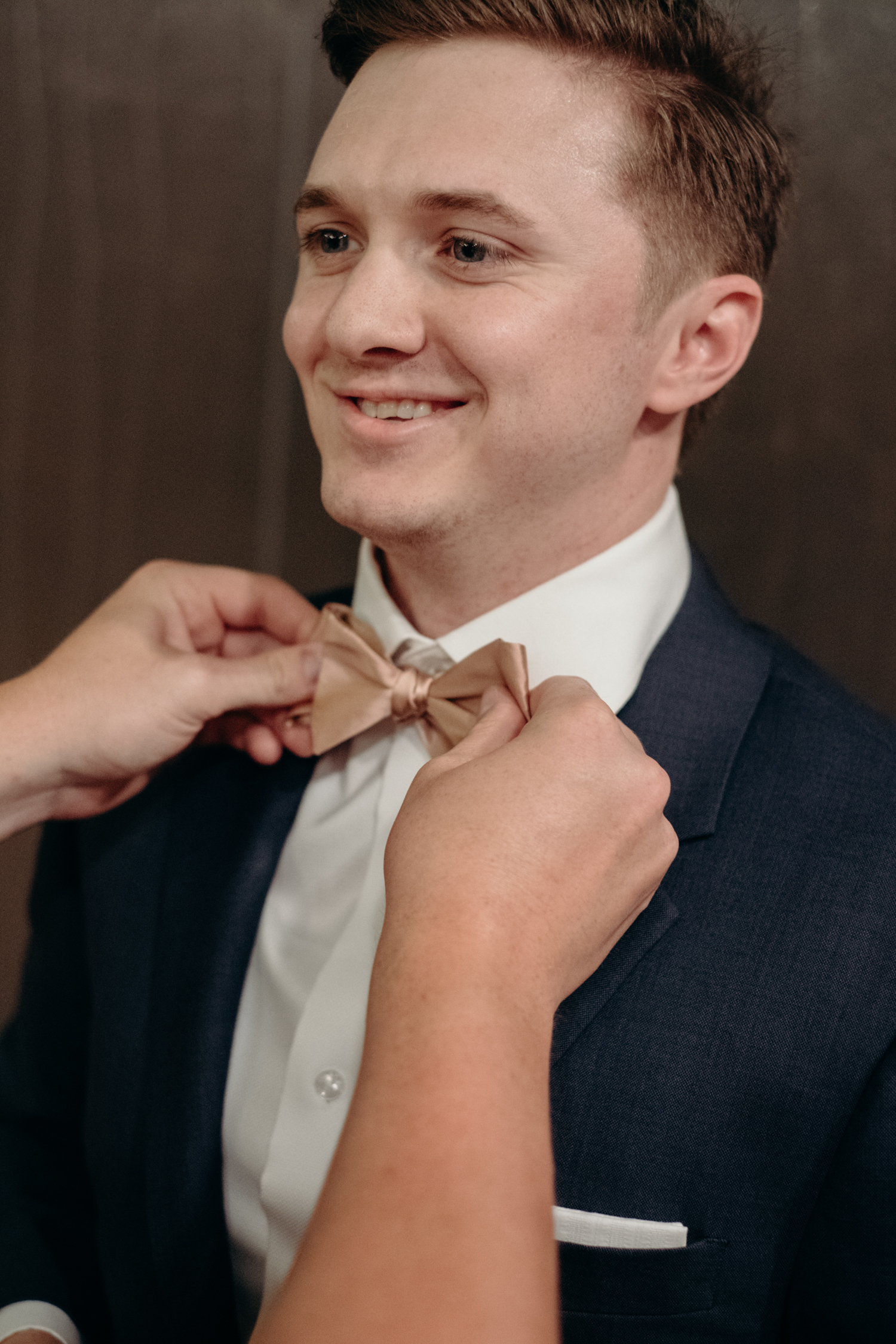 A groom gets his bowtie checked by a groomsman before he walks down the aisle at his wedding at Lansdowne Resort.