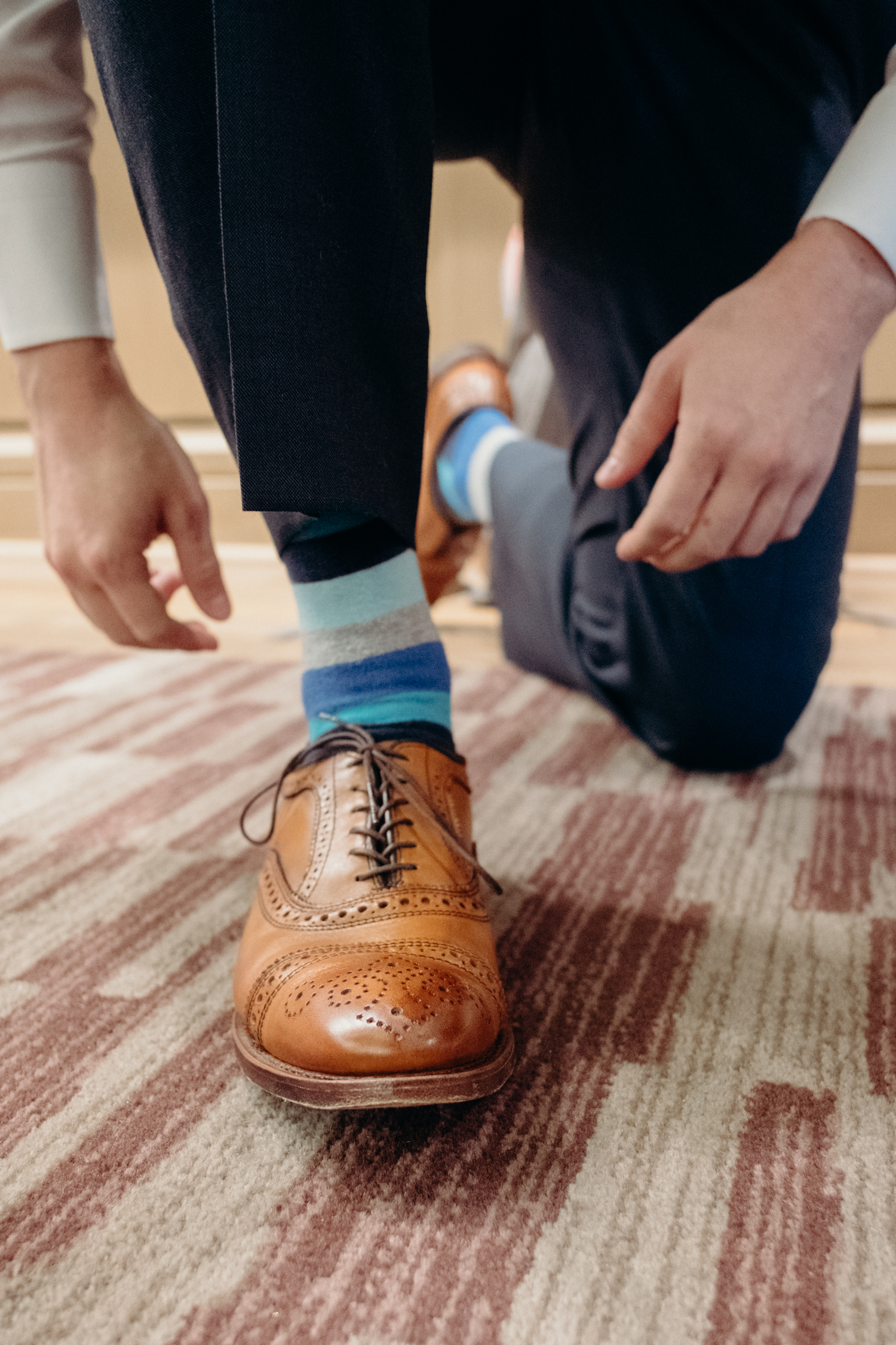 A groom with brown shoes and blue socks leans down to finish tying his shoes before his wedding at Lansdowne Resort.