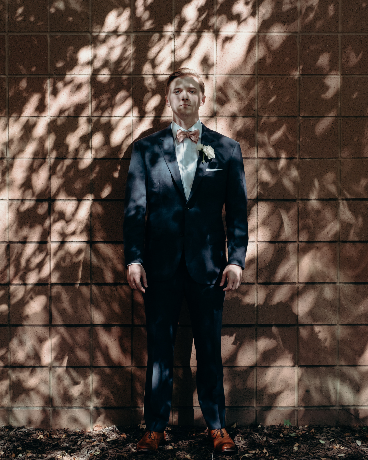 A groom stands in dappled light at Lansdowne resort before his wedding at Lansdowne Resort.