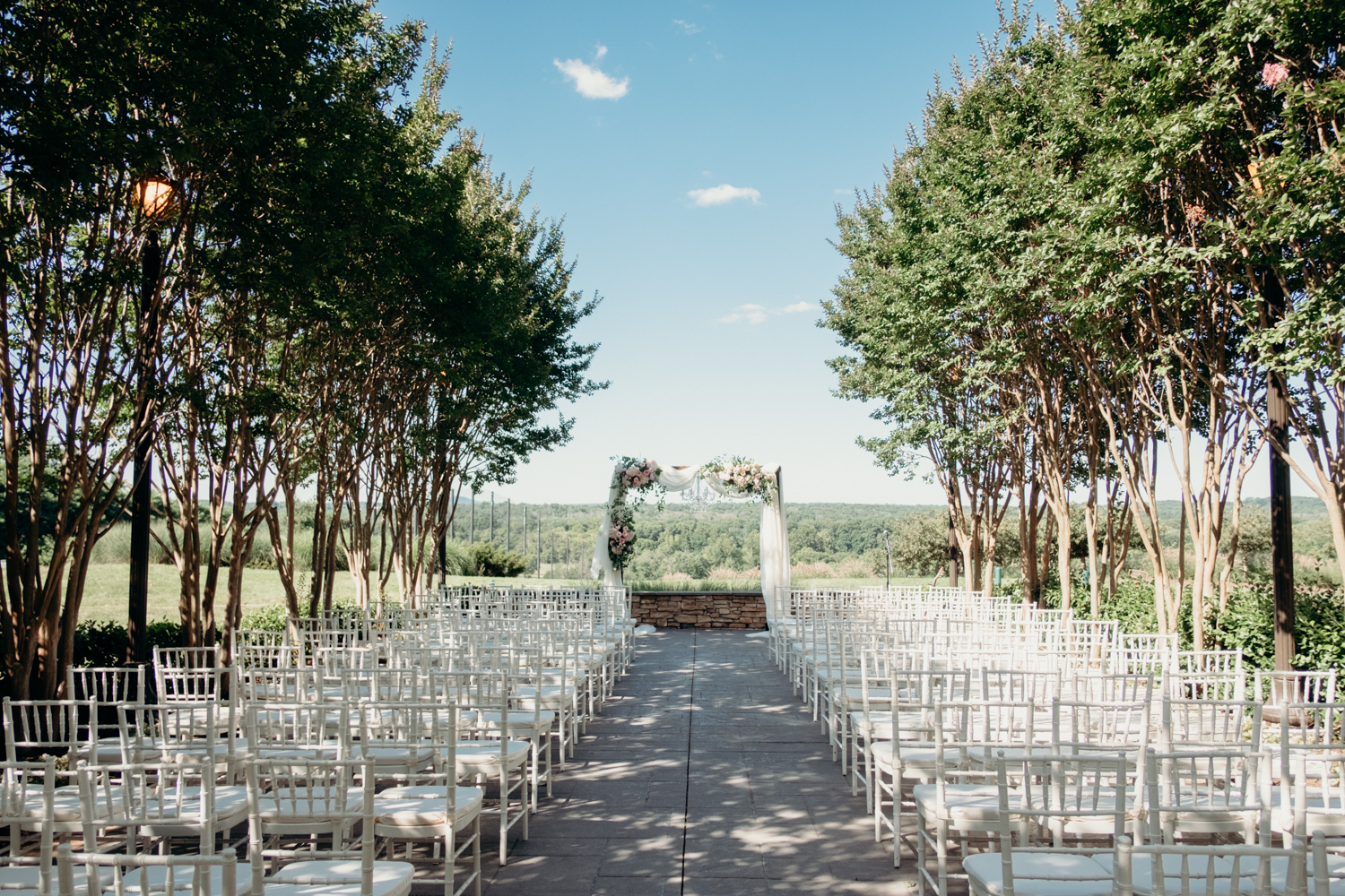 Rows of white chairs with a center aisle leads up to an arbor decorated with while fabric and flowers for a wedding at Lansdowne Resort.