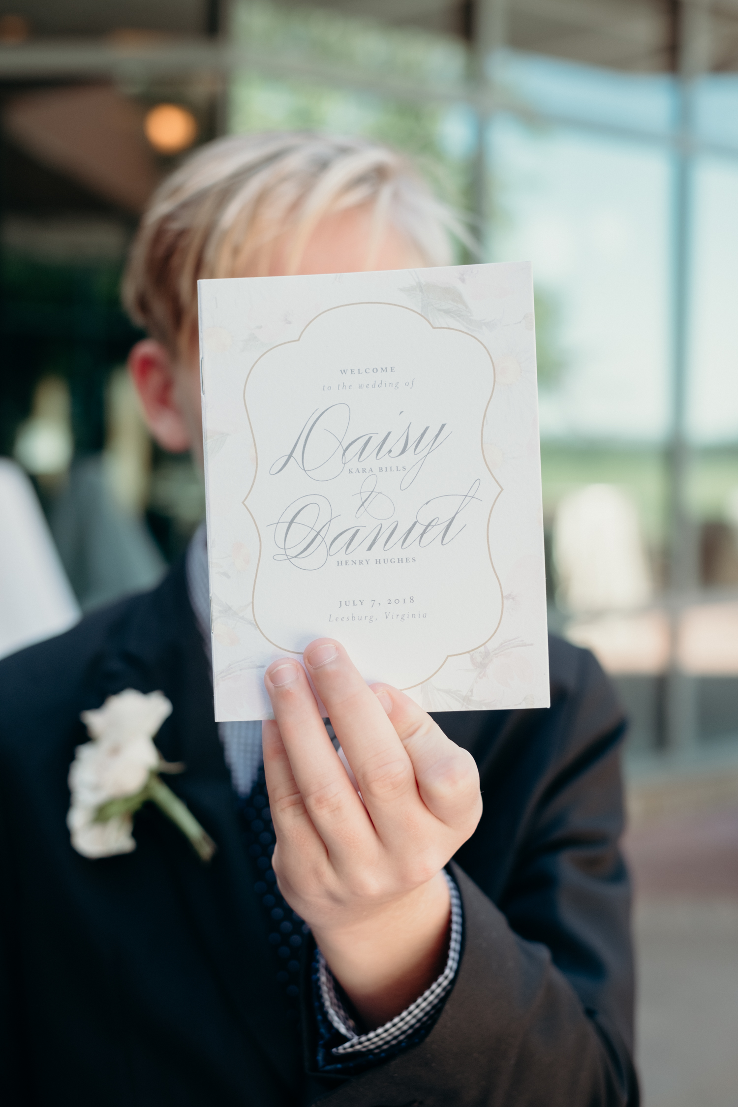 A boy holds up the program for a wedding ceremony at Lansdowne Resort.