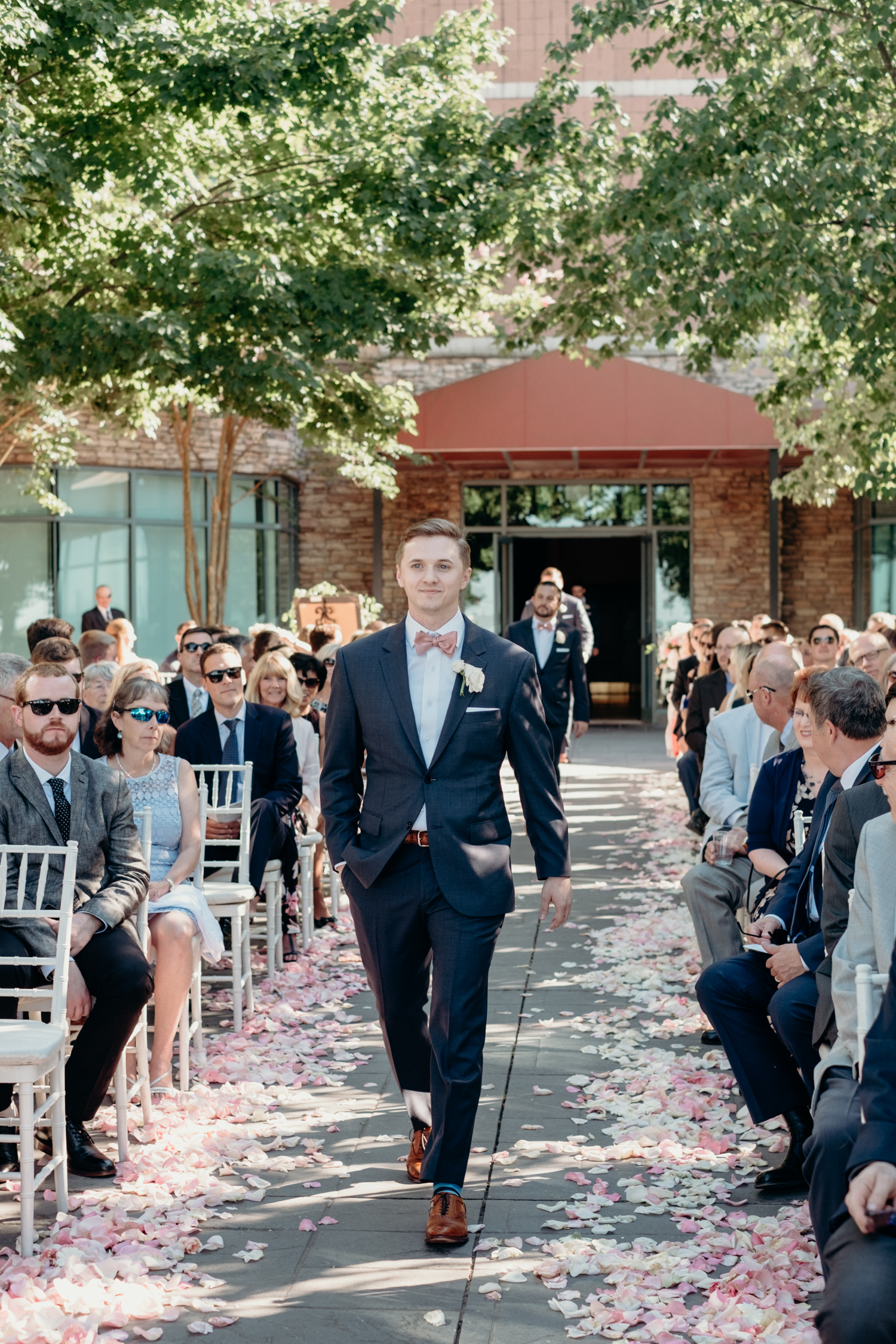 A groom walks up an aisle strewn with petals for this wedding ceremony at Lansdowne Resort.