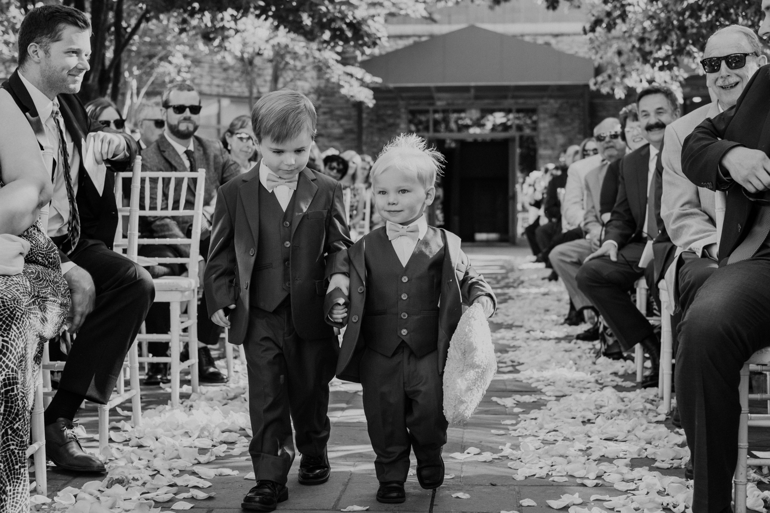 A pair of ring bearers in suits and bowties walk up the aisle at a wedding ceremony at Lansdowne Resort.